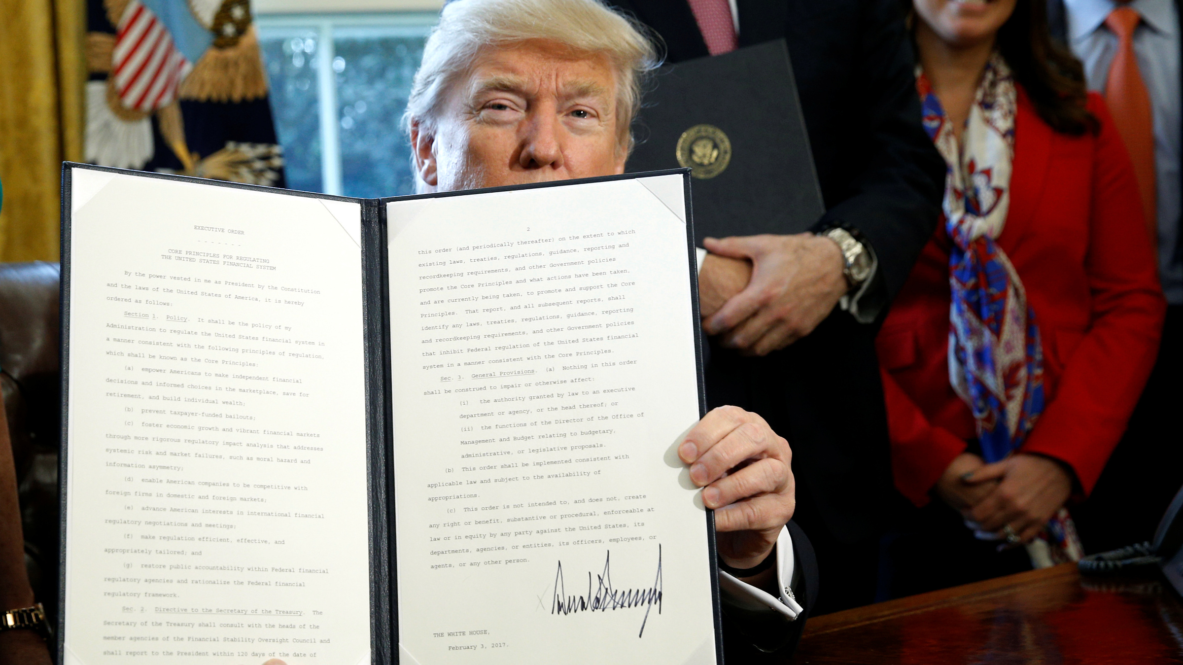 After signing, U.S. President Donald Trump holds up an executive order rolling back regulations from the 2010 Dodd-Frank law on Wall Street reform at the White House in Washington February 3, 2017.