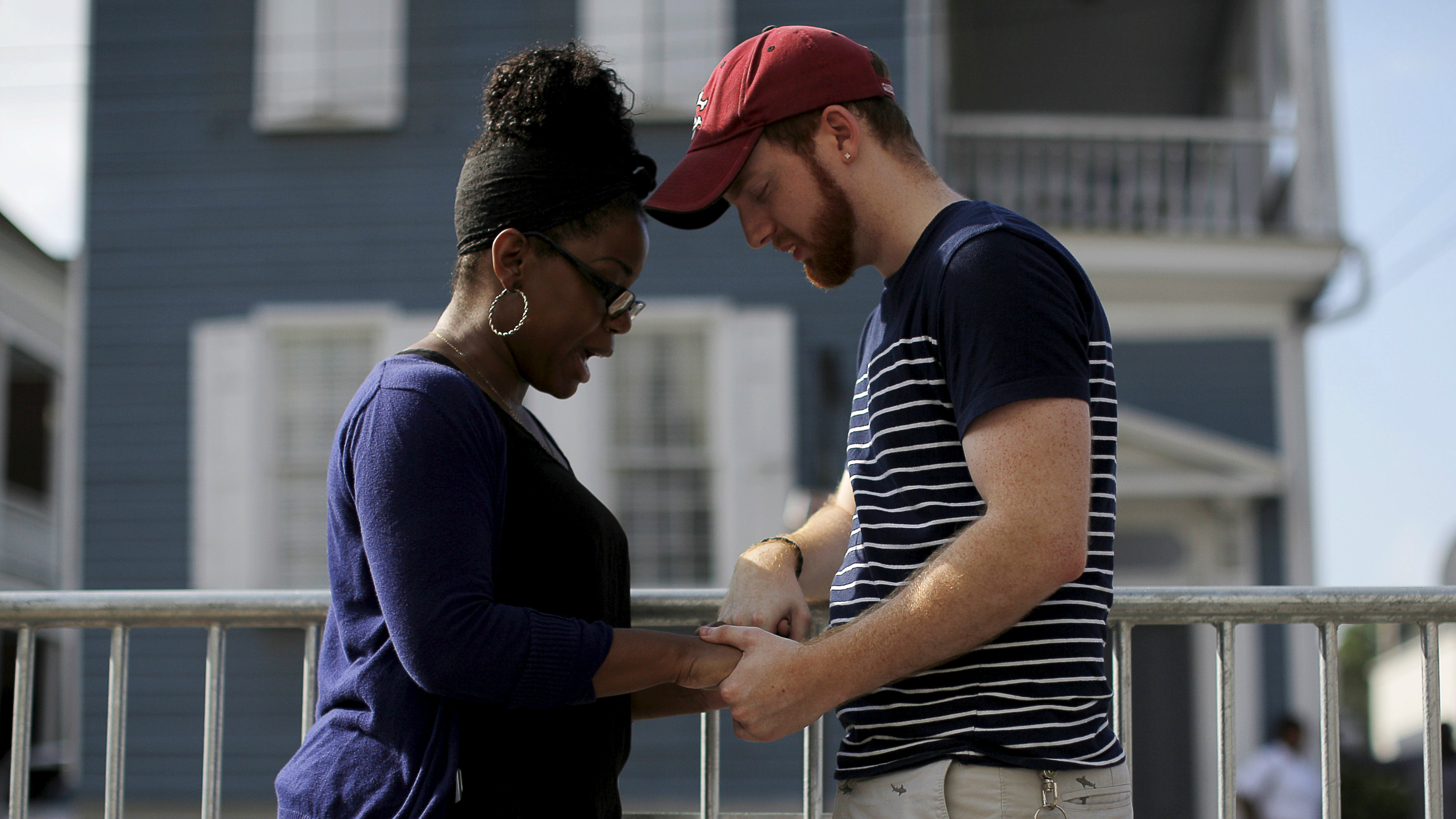Michael Lopez (R) and a woman who asked not to be identified pray outside the Emanuel African Methodist Episcopal Church in Charleston, South Carolina June 20, 2015, three days after a mass shooting which left nine people dead during a bible study at the church. REUTERS/Brian Snyder