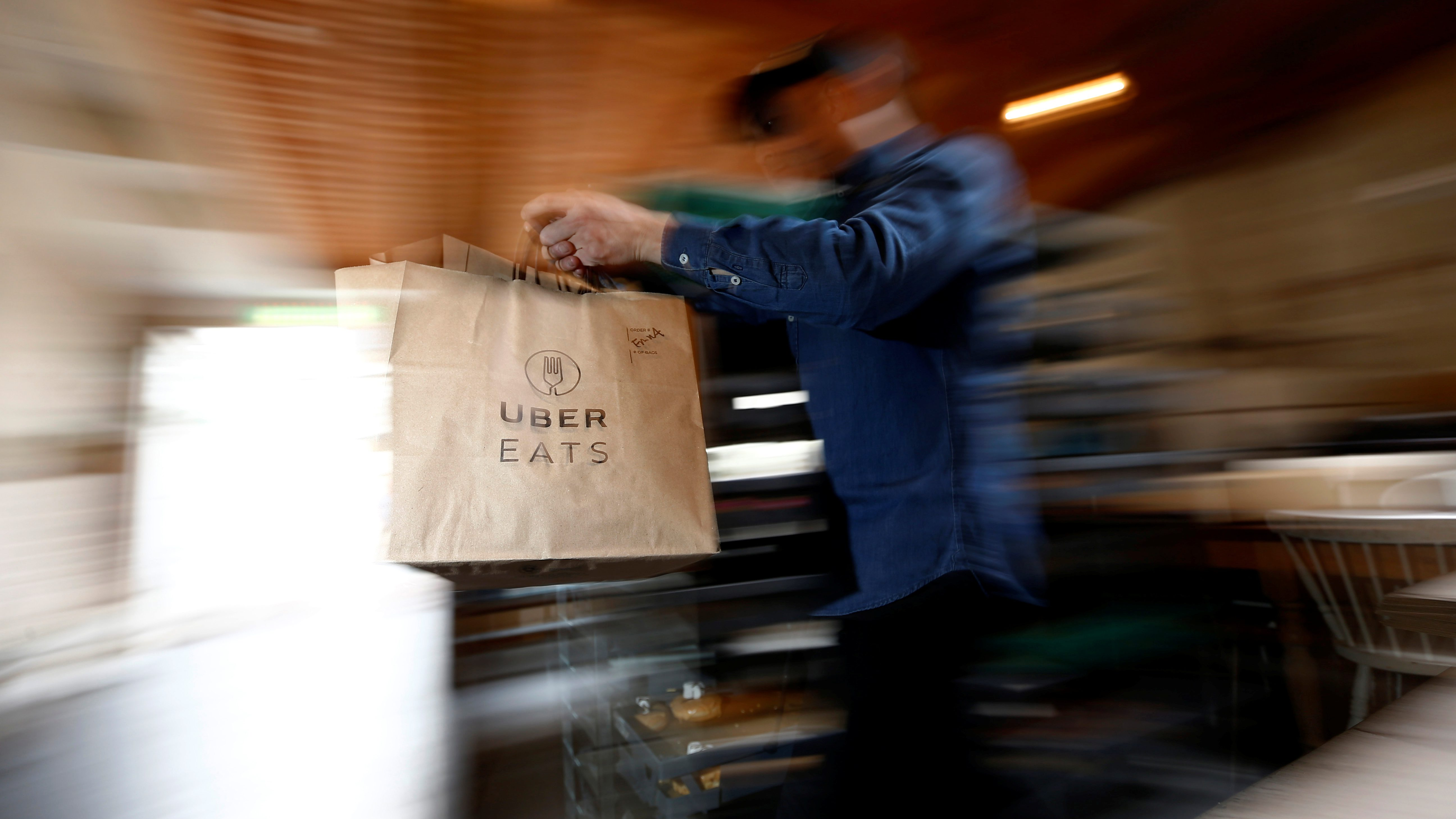A bag of donuts destined for delivery via Uber Eats is rushed to a driver from a kitchen in Sydney August 12, 2016. Picture taken August 12, 2016. REUTERS/Jason Reed   - RTX2NU3U