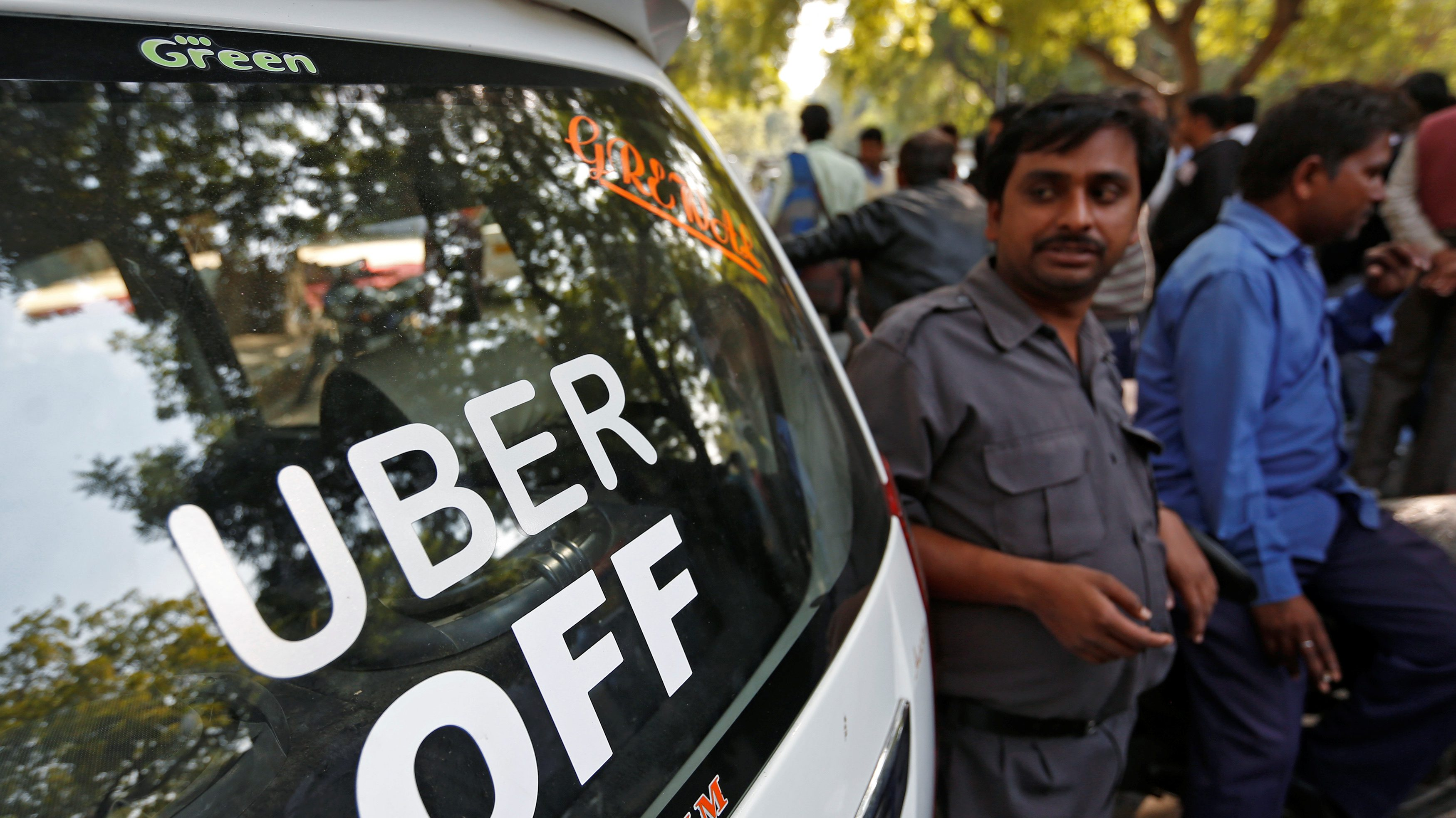 Uber and Ola drivers stand next to their parked vehicle's during a protest in New Delhi