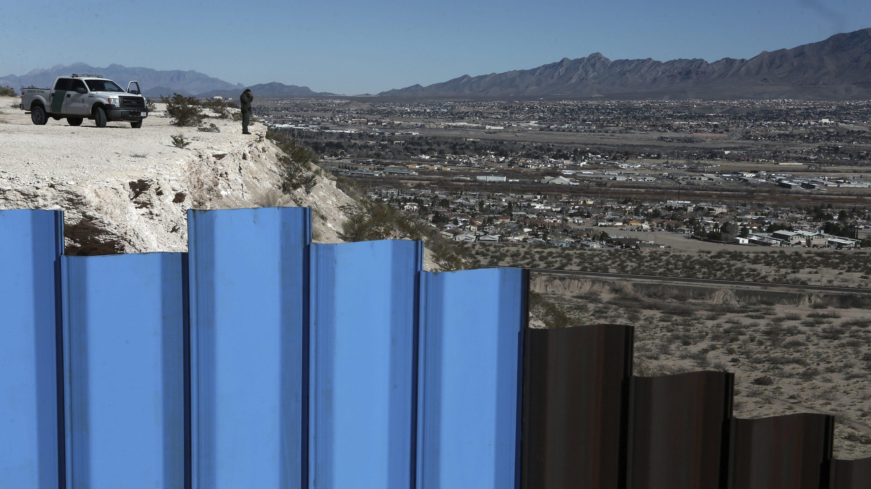 a US border patrol observes the Mexico-US border fence