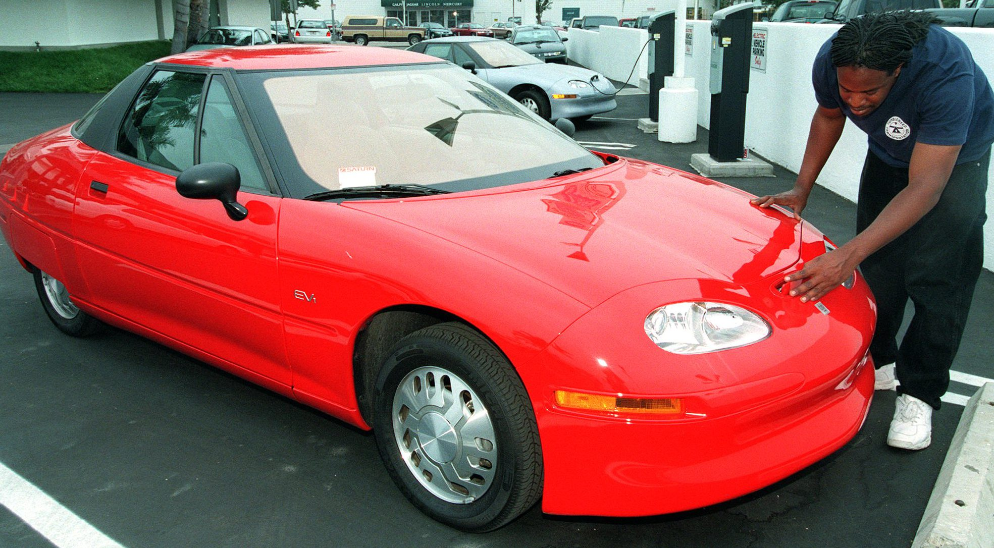 Arthur Pride views an EV1 electric vehicle at a Saturn dealership in Los Angeles Tuesday, May 20, 1997.   Although some 1,100 of the vehicles were produced since 1996 and leased to drivers in California and Arizona, almost all were destroyed once the leases ran out.