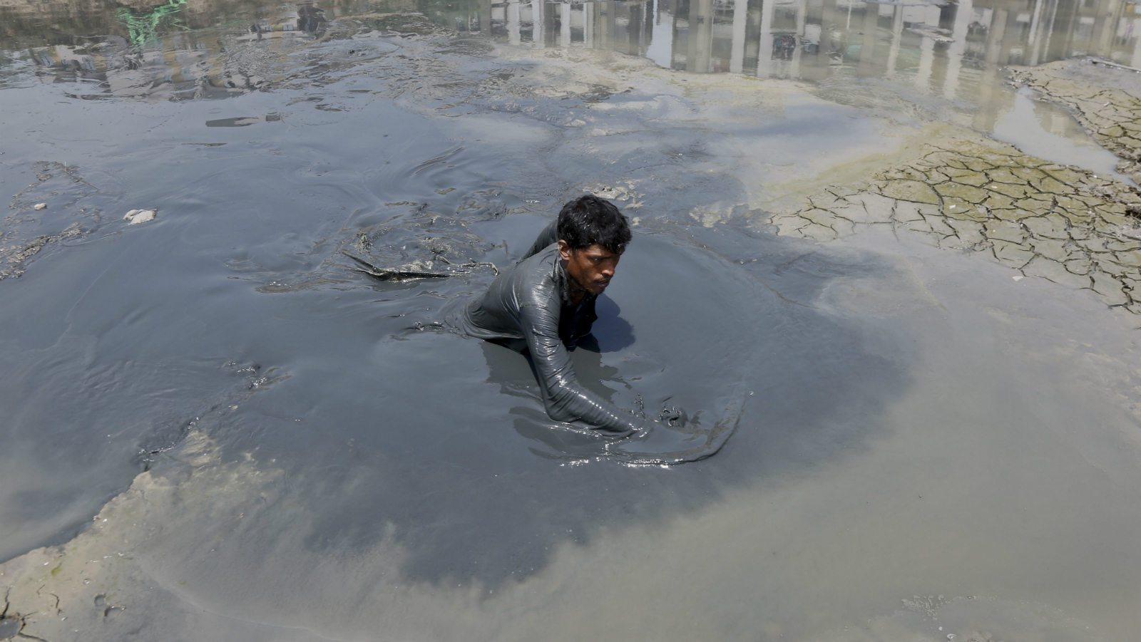 An Indian municipal worker searches for fish prior to rescuing them from a dried lake at Ratanpura in Ahmadabad, Gujarat, India, Wednesday, May 11, 2016. Much of India is reeling under a weekslong heat wave and severe drought conditions that have decimated crops, killed livestock and left at least 330 million Indians without enough water for their daily needs.Rivers, lakes and dams have dried up in parts of the western states of Maharashtra and Gujarat, and overall officials say that groundwater reservoirs are at just 22 percent capacity.