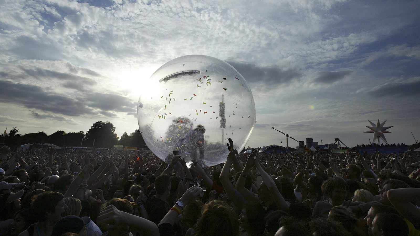 U.S. singer Wayne Coyne of the Flaming Lips rolls into the crowd in a giant bubble at the O2 Wireless Festival in Hyde Park, London on June 23, 2006. The festival runs until June 25. REUTERS/Leon Neal  (BRITAIN) - RTR1ESR5