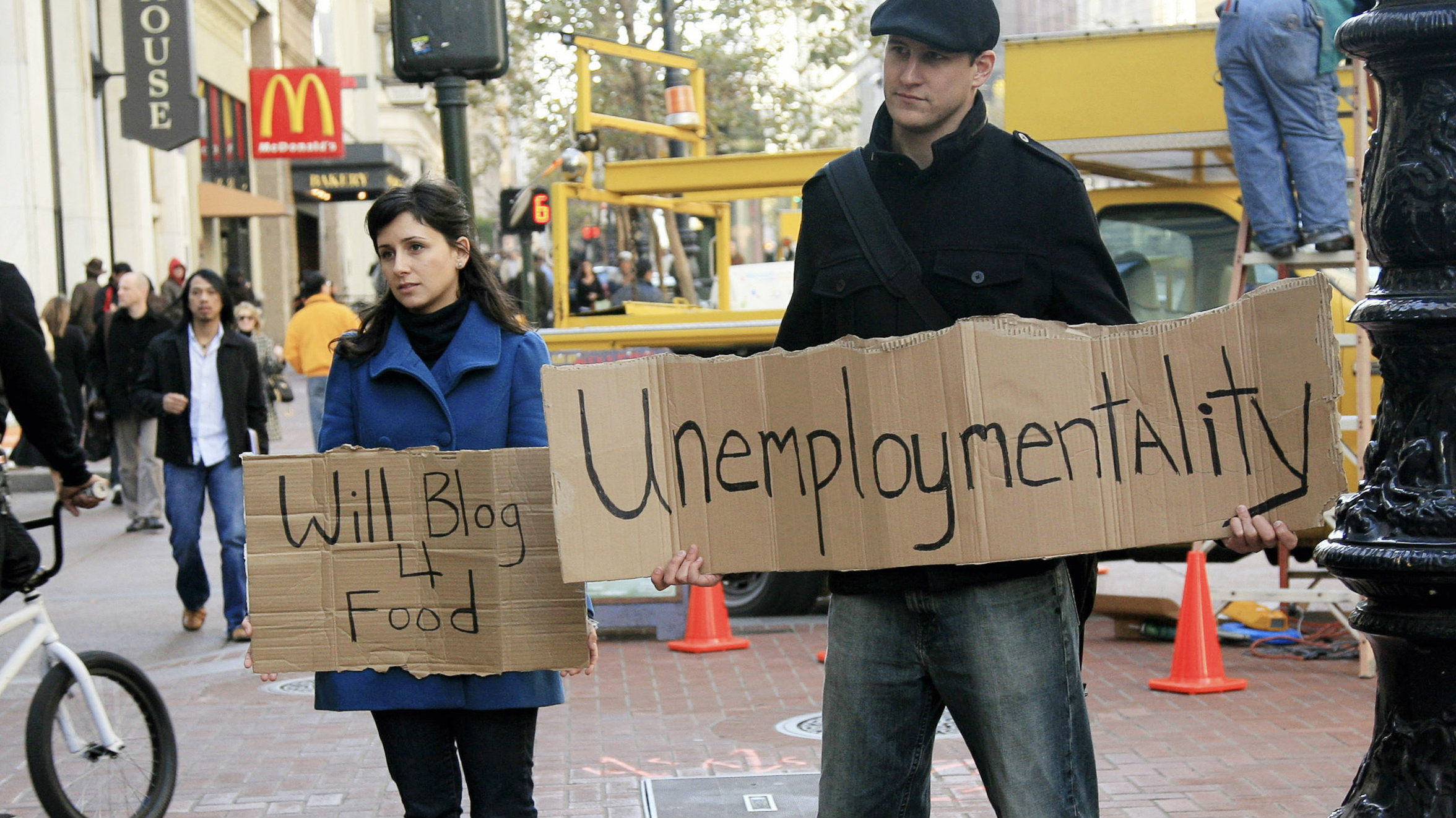 """Tania Khadder (L), 29, and John Henion, 32, both unemployed online journalists, hold signs announcing a new blog called """"unemploymentality.com"""" along Market Street in San Francisco, California December 9, 2008. Both have been laid off from their media jobs and are starting the blog to document the current economic situation from their point of view, and others in similar situations. REUTERS/Robert Galbraith (UNITED STATES)"""