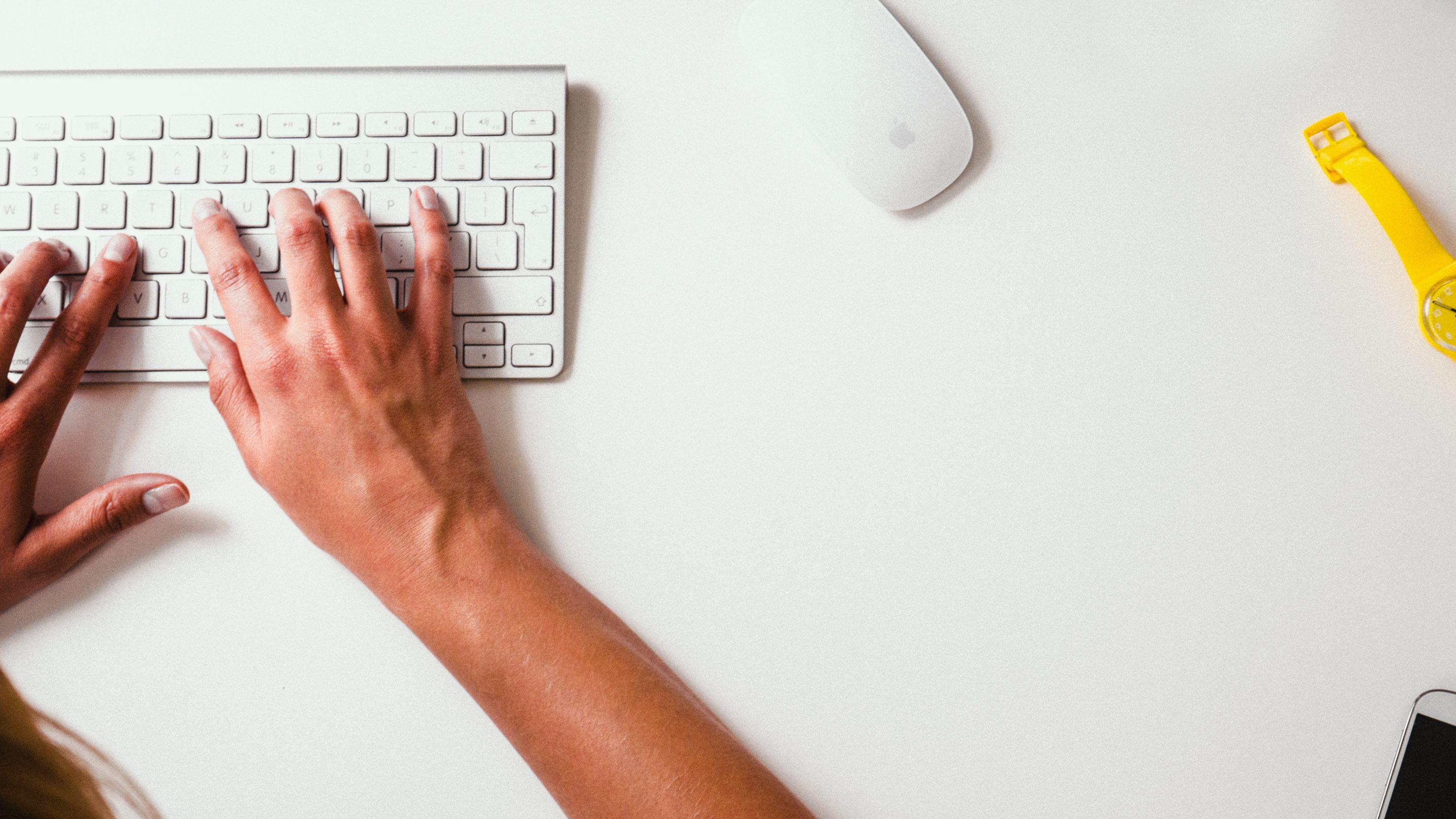 woman typing on white desk