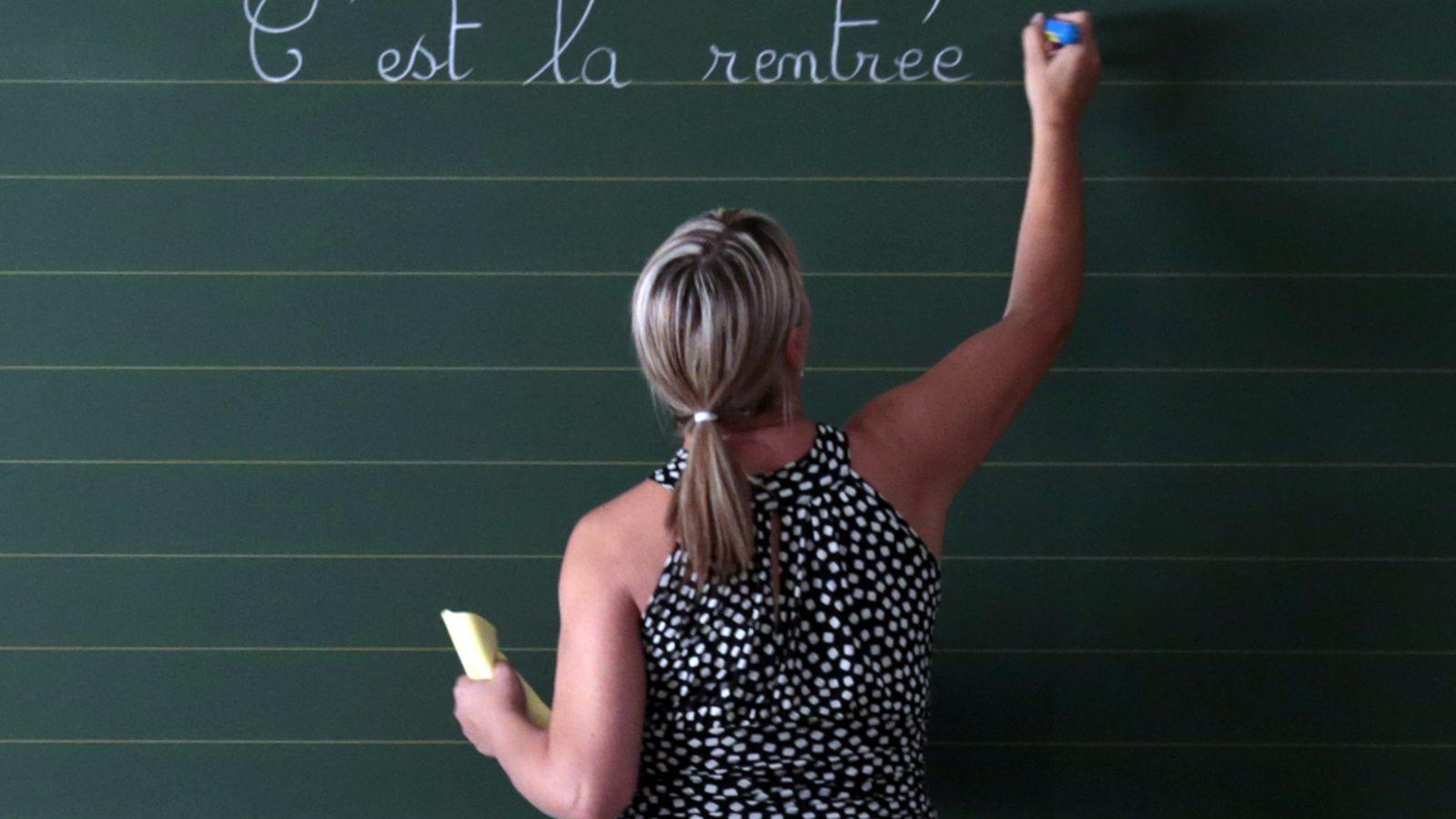 A woman writes on a blackboard.