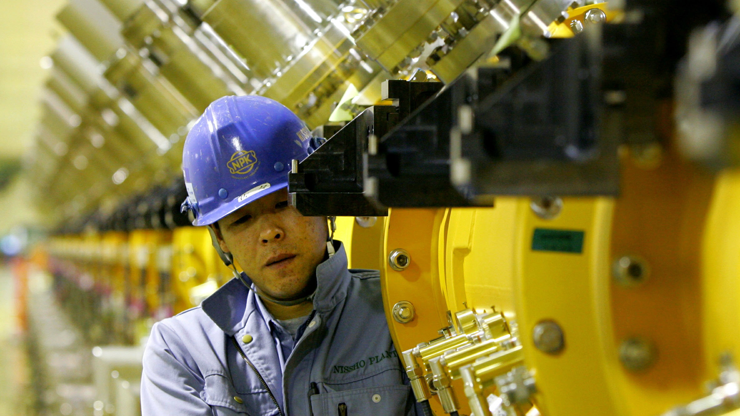 "A worker works on a part of a 330 meters proton linear accelerator at a Japan Proton Accelerator Research Complex ""J-PARC"" facility in Tokai village, about 130 km (81 miles) northeast of [Tokyo] May 16, 2006. The facility, which is in the process of being built jointly by the High Energy Accelerator Research Organization and the Japan Atomic Energy Agency, is expected to start its operations in 2008. J-PARC aims to pursue frontier science in particle physics, nuclear physics, materials science, life science and nuclear technology, using a new proton accelerator complex at the highest beam power in the world, the facility officials said."
