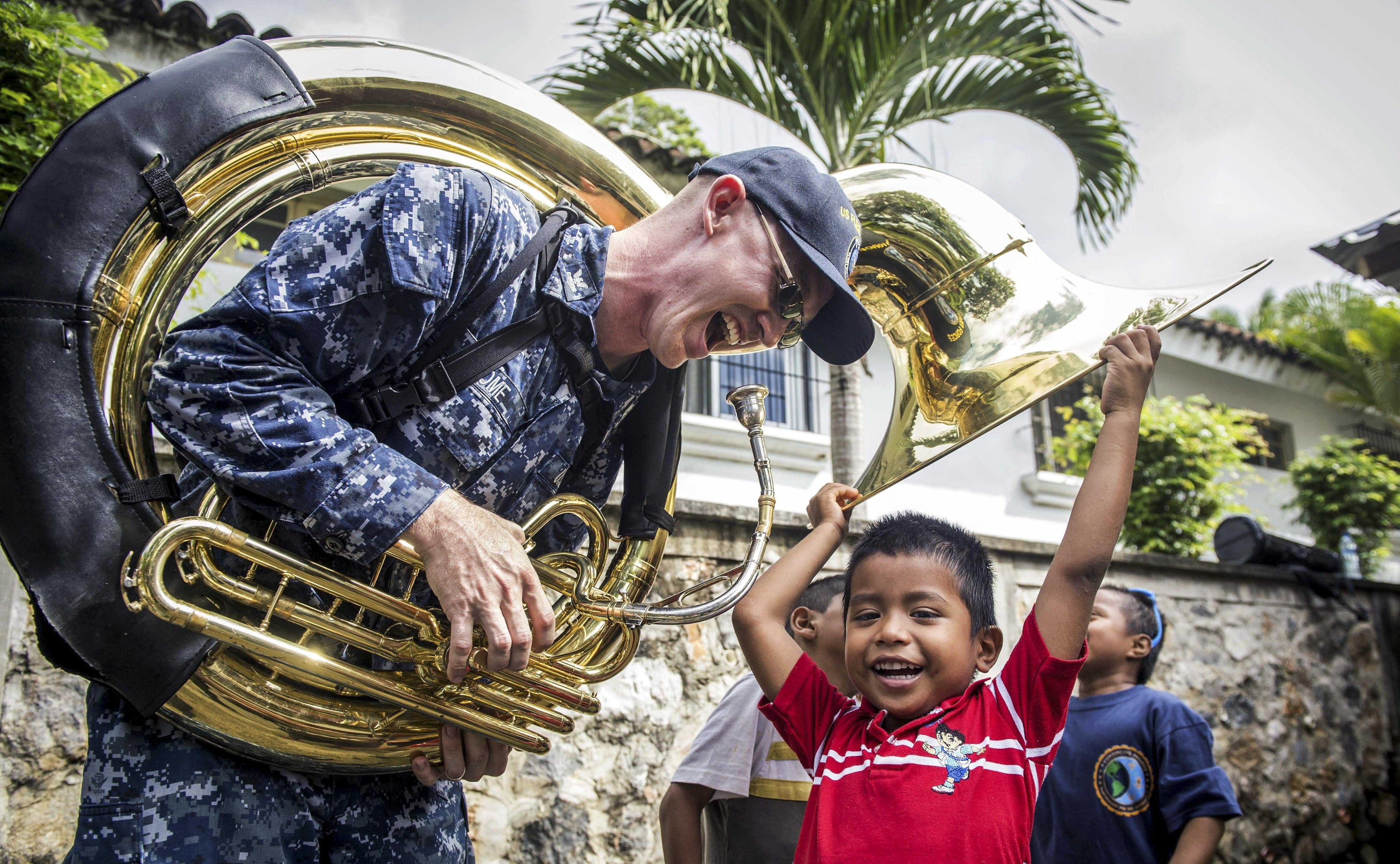 Navy Petty Officer plays with an child whilst wearing a helicon.