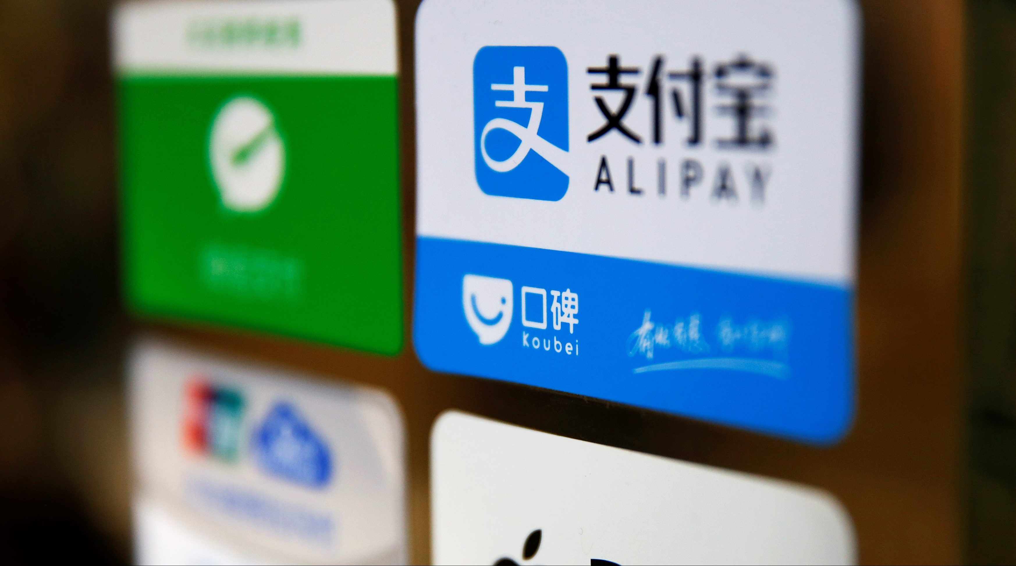 An Alipay logo is seen among other paying method stickers on the doors of a restaurant at the Beijing Railway Station in central Beijing January 13, 2017.