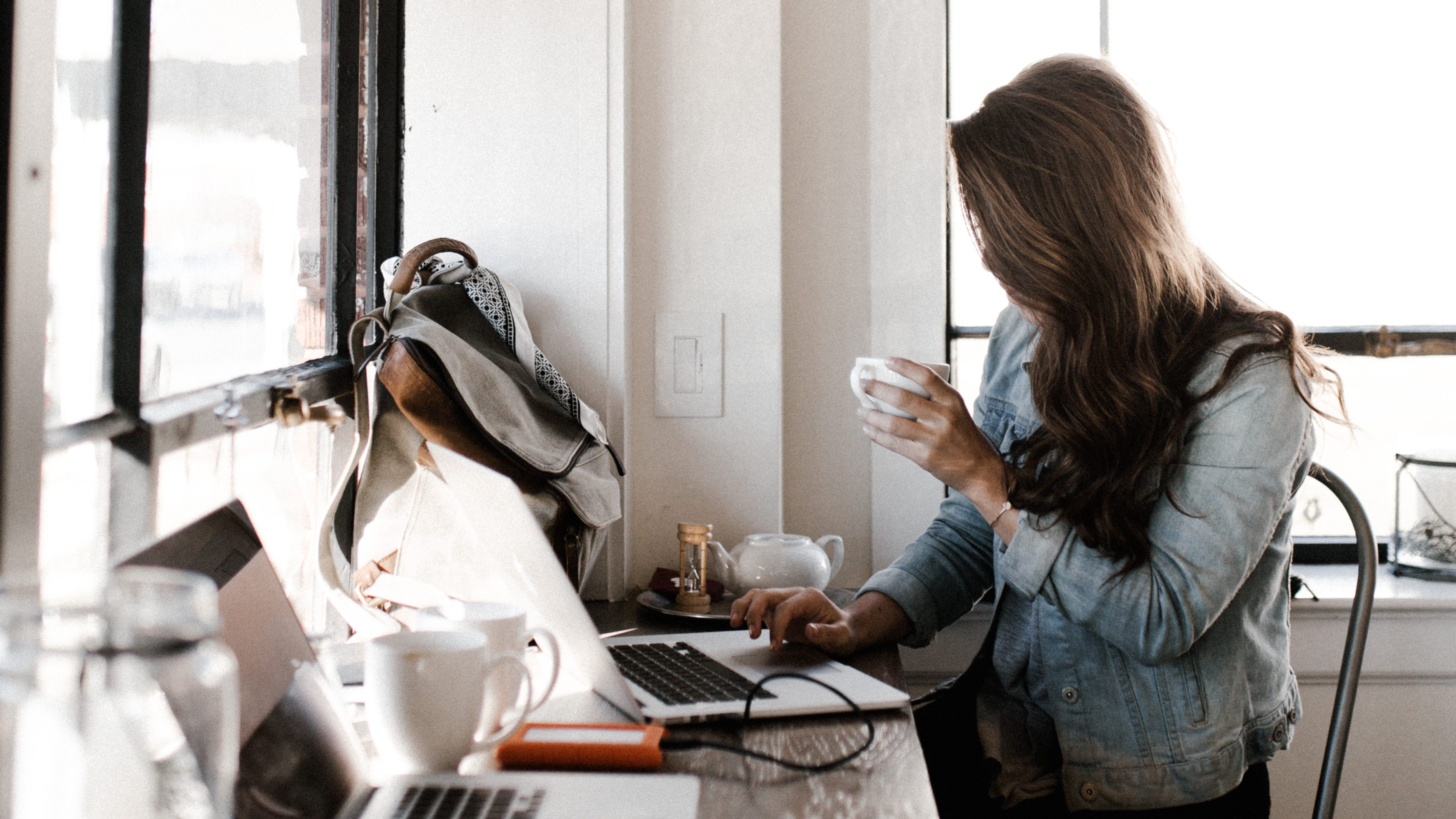 A woman drinks coffee checking her laptop