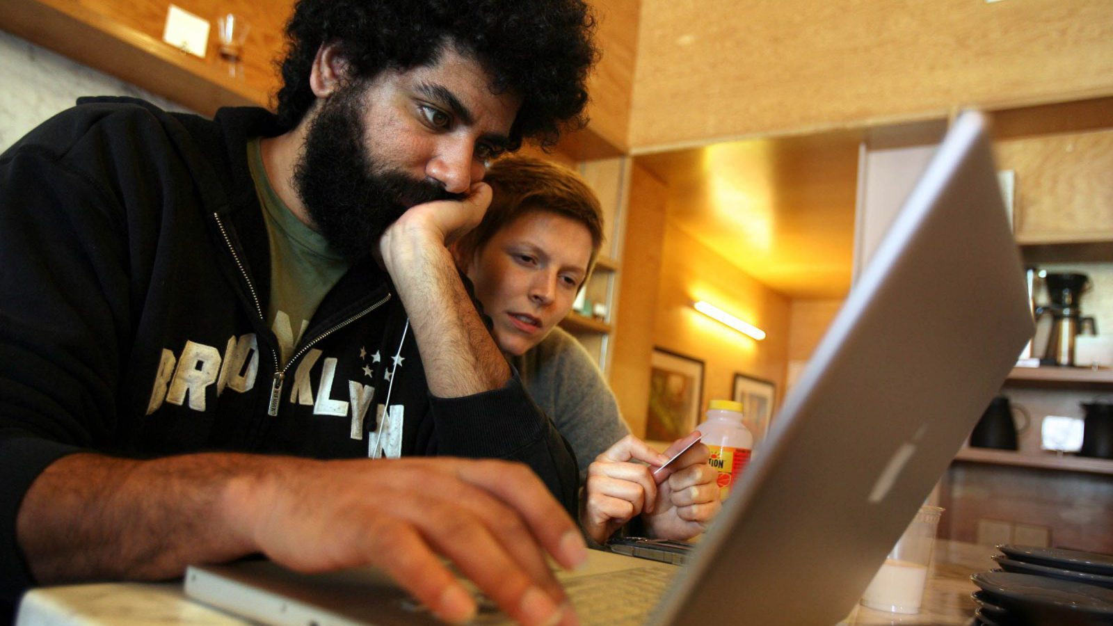 Writer and actor Mousa Kraish, left, looks at his computer with friend Deanna Mustard at the Intelligentsia coffee shop in Los Angeles, Wednesday Feb. 13, 2008. Kraish is not a Writers Guild of America member. Hollywood writers are back to work after ending their three-month strike.