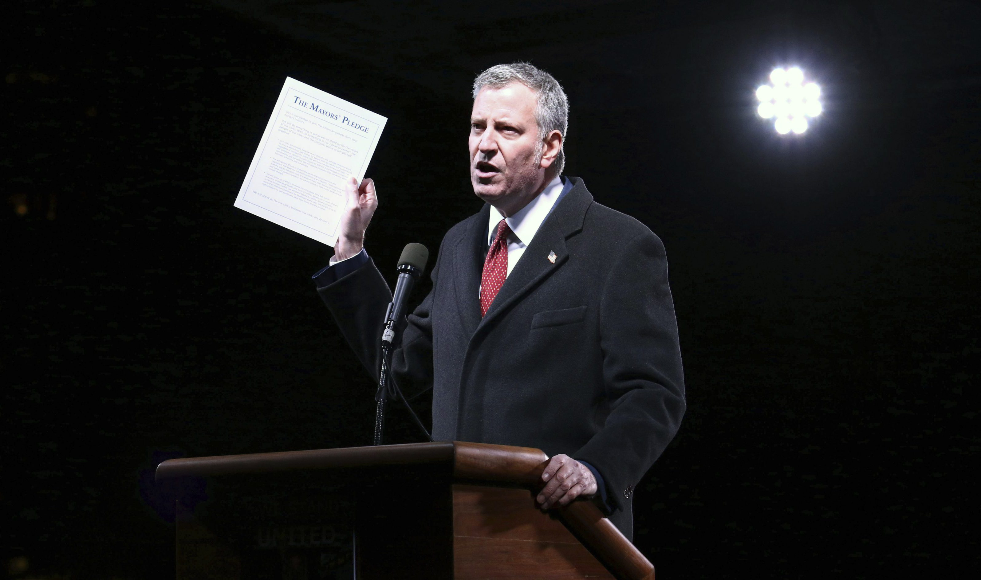 """FILE - In this Jan. 19, 2017 file photo, New York Mayor Bill de Blasio holds up a documented titled """"The Mayors' Pledge"""" during the """"We Stand United: New York Rally to Protect Shared Values"""" event in New York. Blasio said Wednesday, Jan. 25, 2017 that his city will continue to protect undocumented migrants, in a clear response to executive orders signed by President Donald Trump hours earlier which began the process of blocking federal aid to cities that protect foreigners living in the U.S. without permission. (Photo by Greg Allen/Invision/AP, File)"""