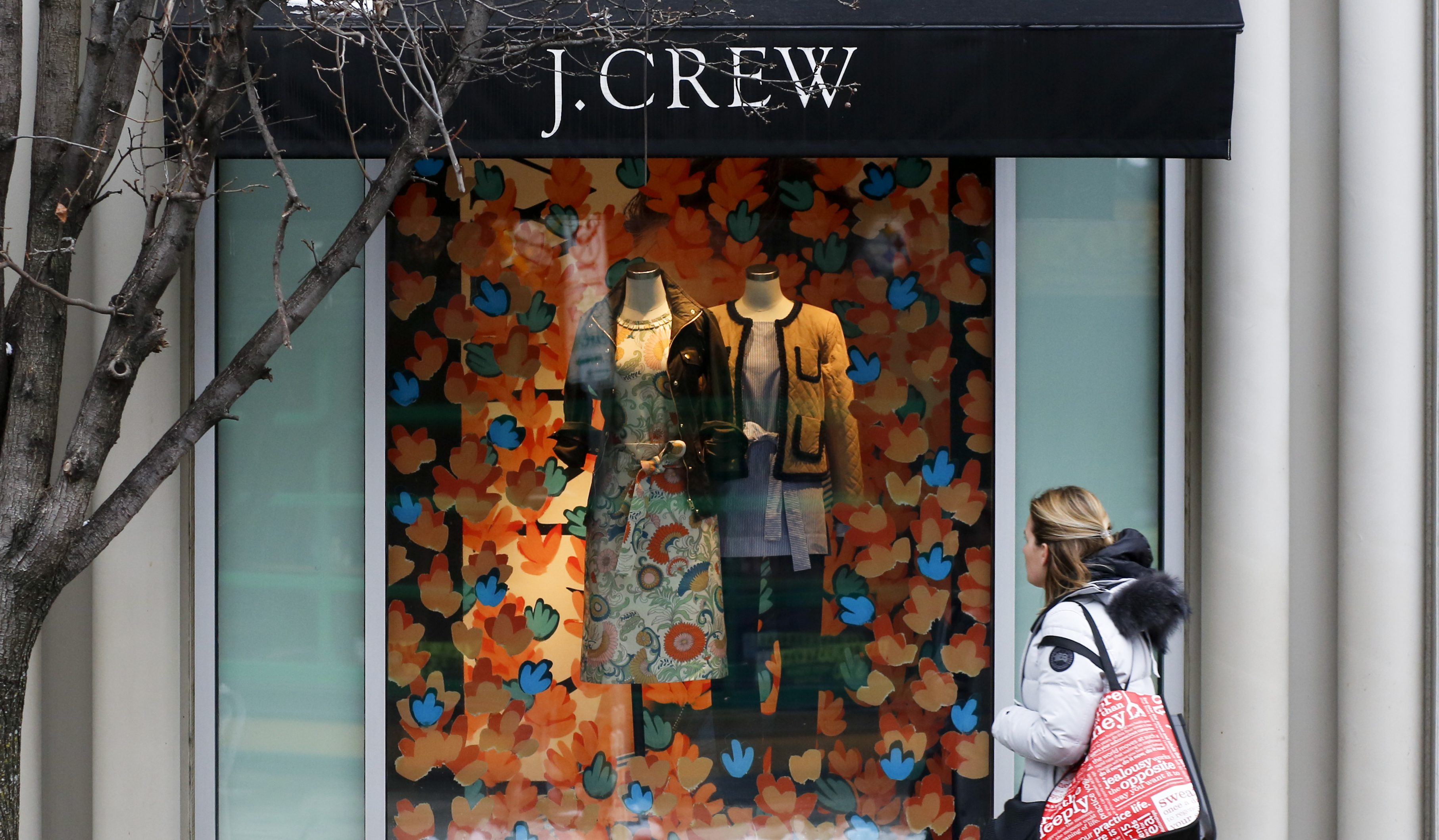 A shopper passes the display in the window of a J.Crew store in the Shadyside shopping district of Pittsburgh Friday, Feb. 10, 2017. (AP Photo/Gene J. Puskar)