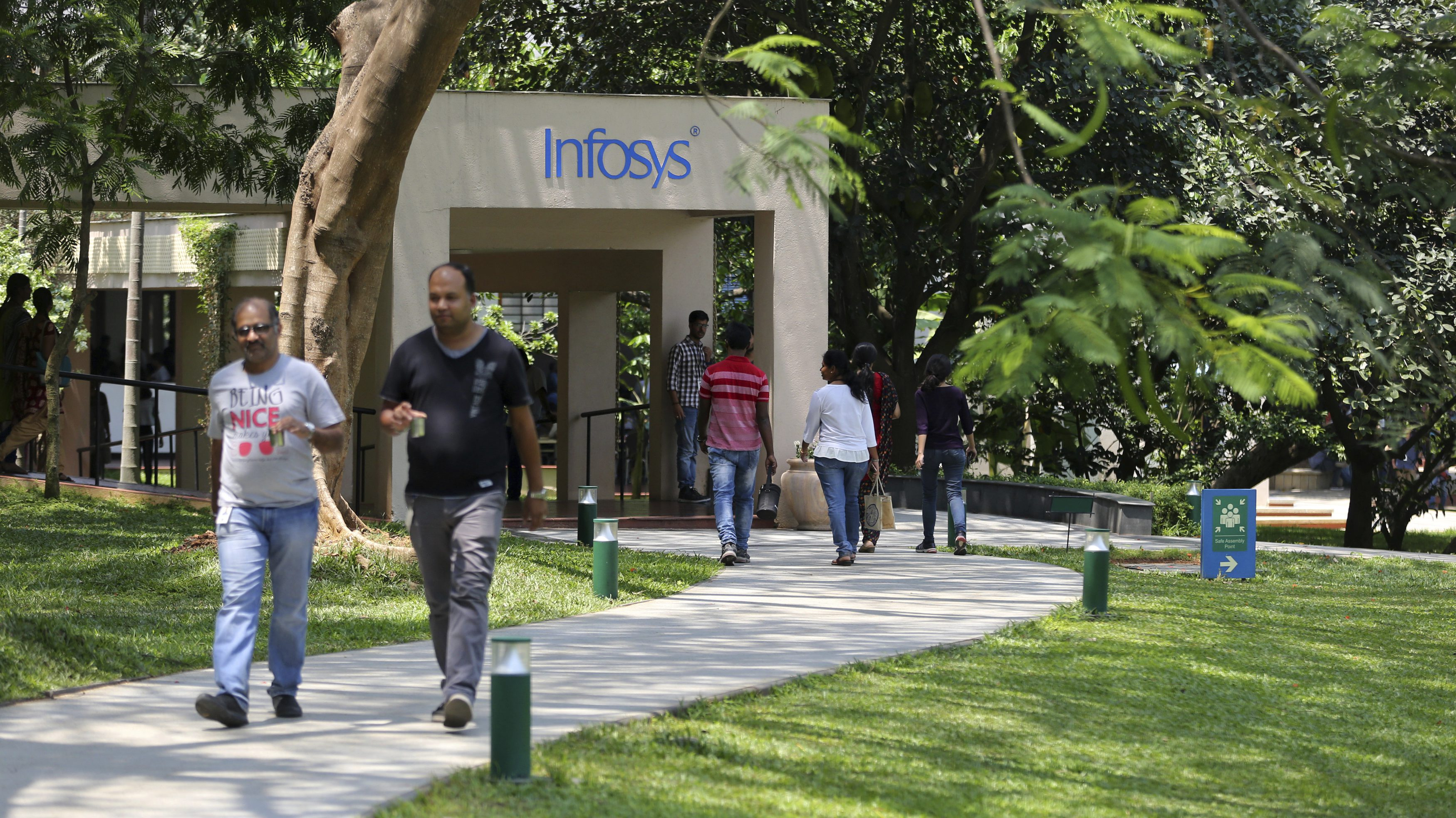 Infosys employees walk inside the company headquarters during a break after their annual financial results were announced in Bangalore, India, Thursday, April 13, 2017. (AP Photo/Aijaz Rahi)