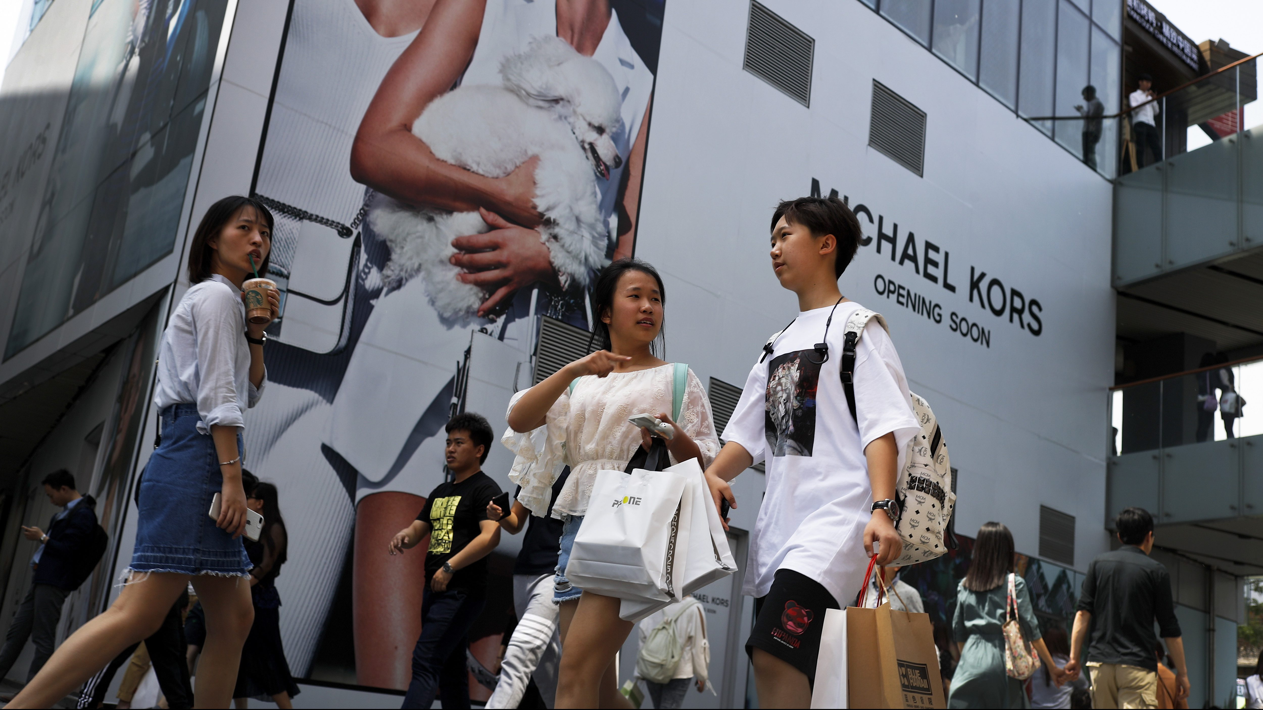 Shoppers walk through the capital city's popular shopping mall in Beijing, Sunday, April 30, 2017. Growth in China's manufacturing sector slowed in April, official data showed Sunday, pointing to an unsteady recovery in the world's second-largest economy. (AP Photo/Andy Wong)