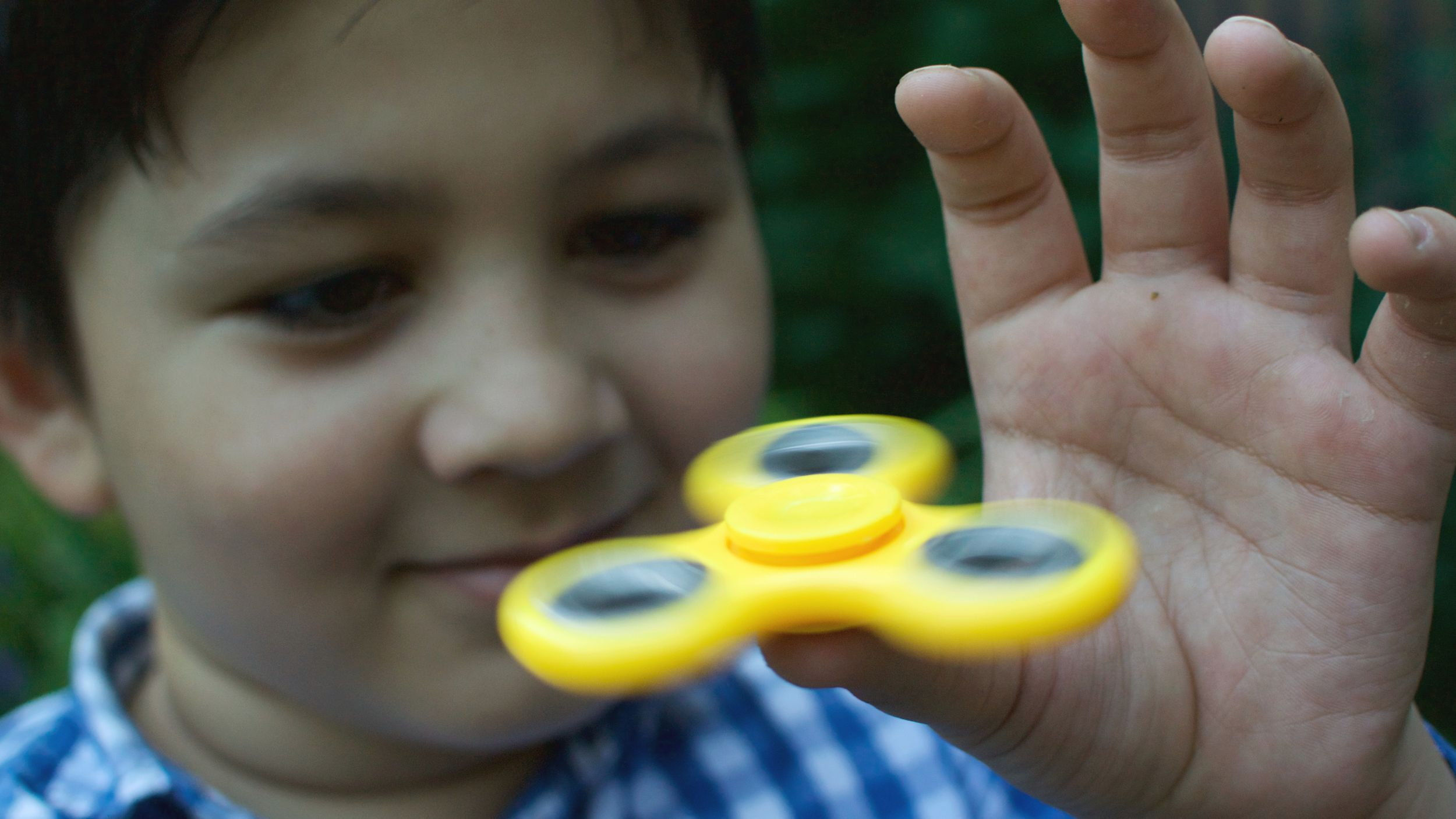A boy plays with a fidget spinner in Moscow, Russia, on Wednesday, July 19, 2017. Russian authorities are investigating fidget spinners after state television reported that opposition activists are using them to attract supporters.
