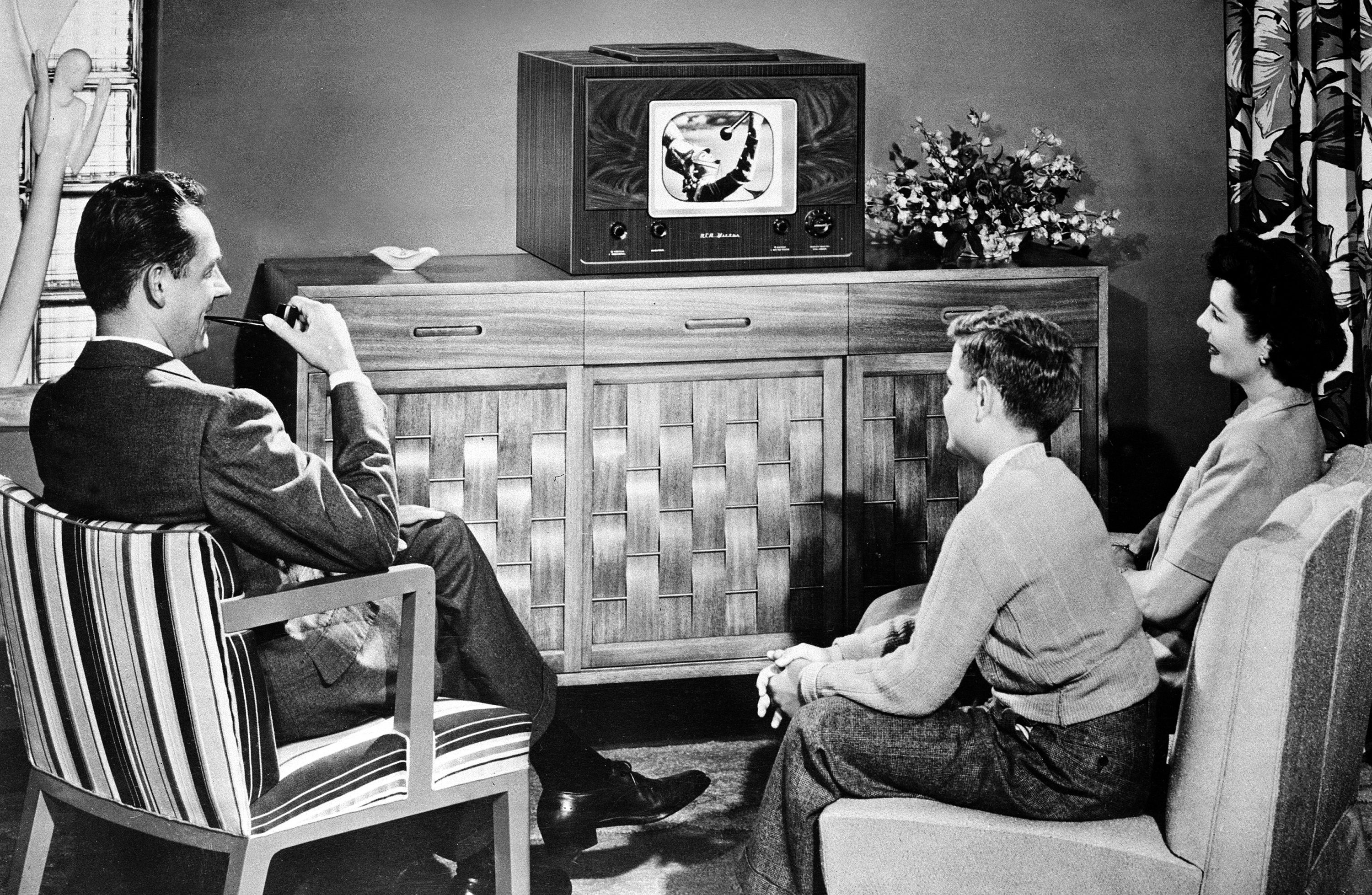 An American family watches a tabletop radio television in 1948.