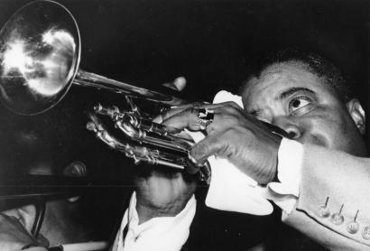American jazz musician Louis Armstrong plays his trumpet.