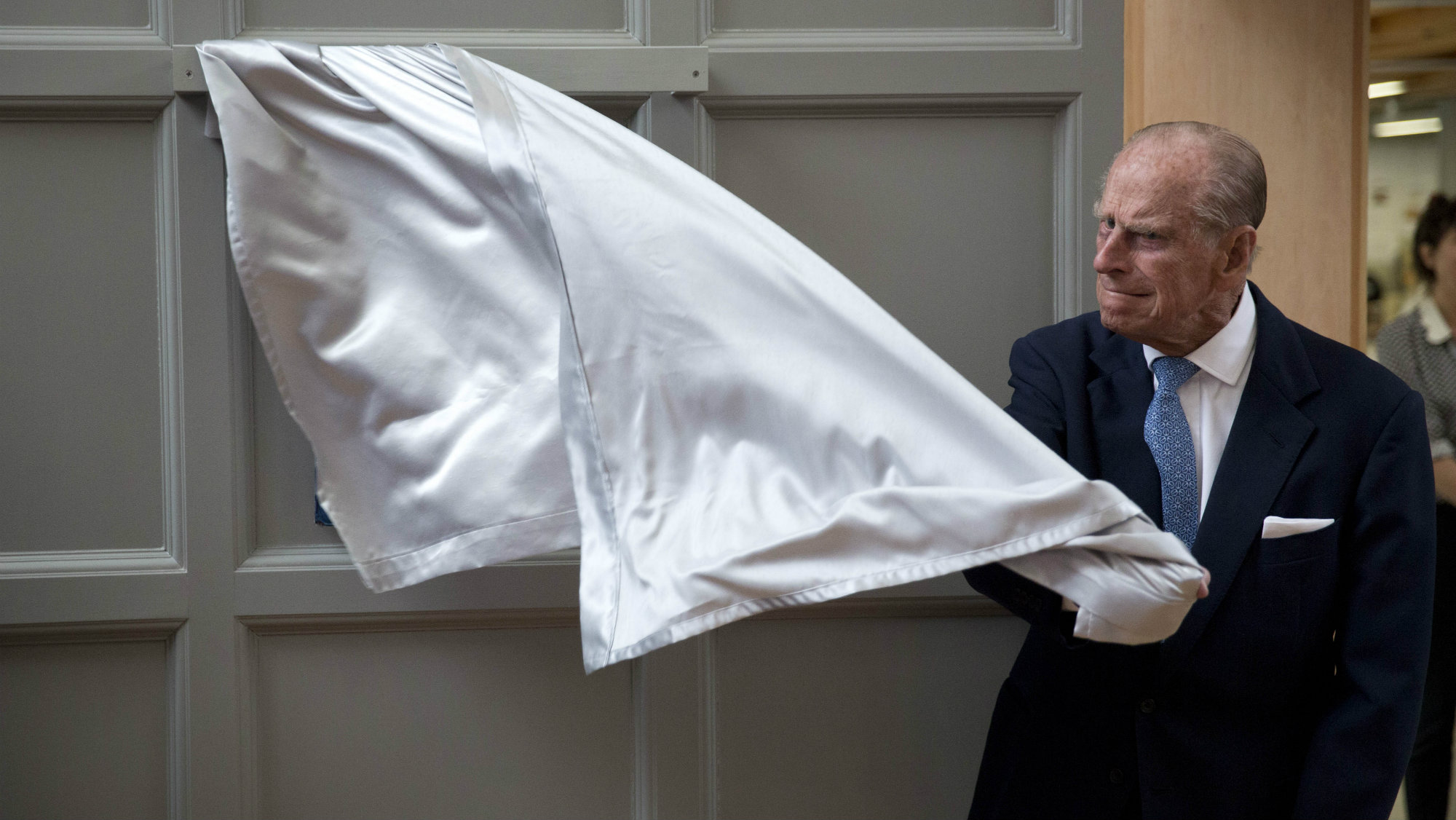 Britain's Prince Philip, the husband of Queen Elizabeth II, pulls the curtain to unveil a plaque at the end of his visit to Richmond Adult Community College in Richmond, south west London, Monday, June 8, 2015.