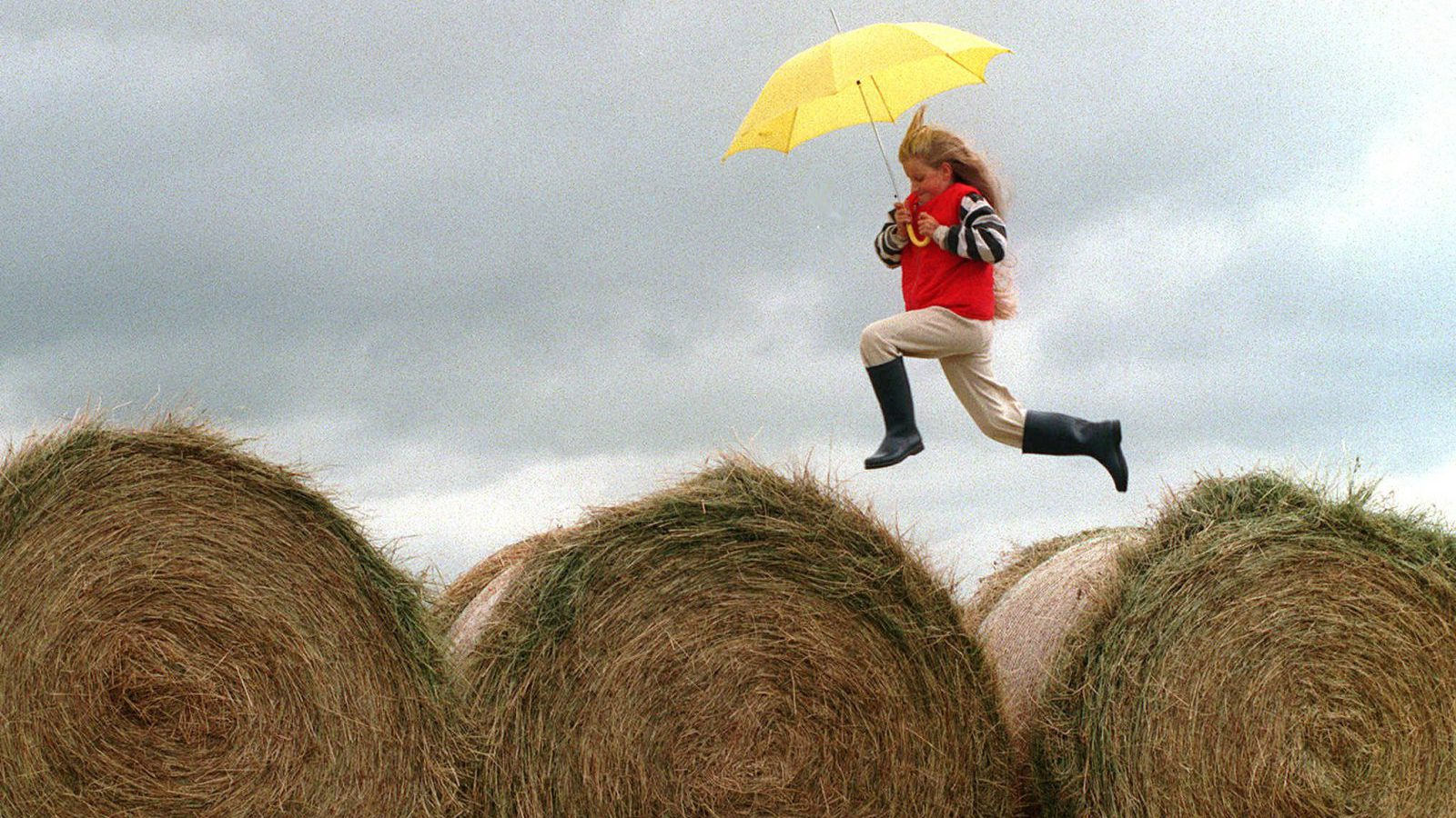 girl with umbrella skipping over hay bales