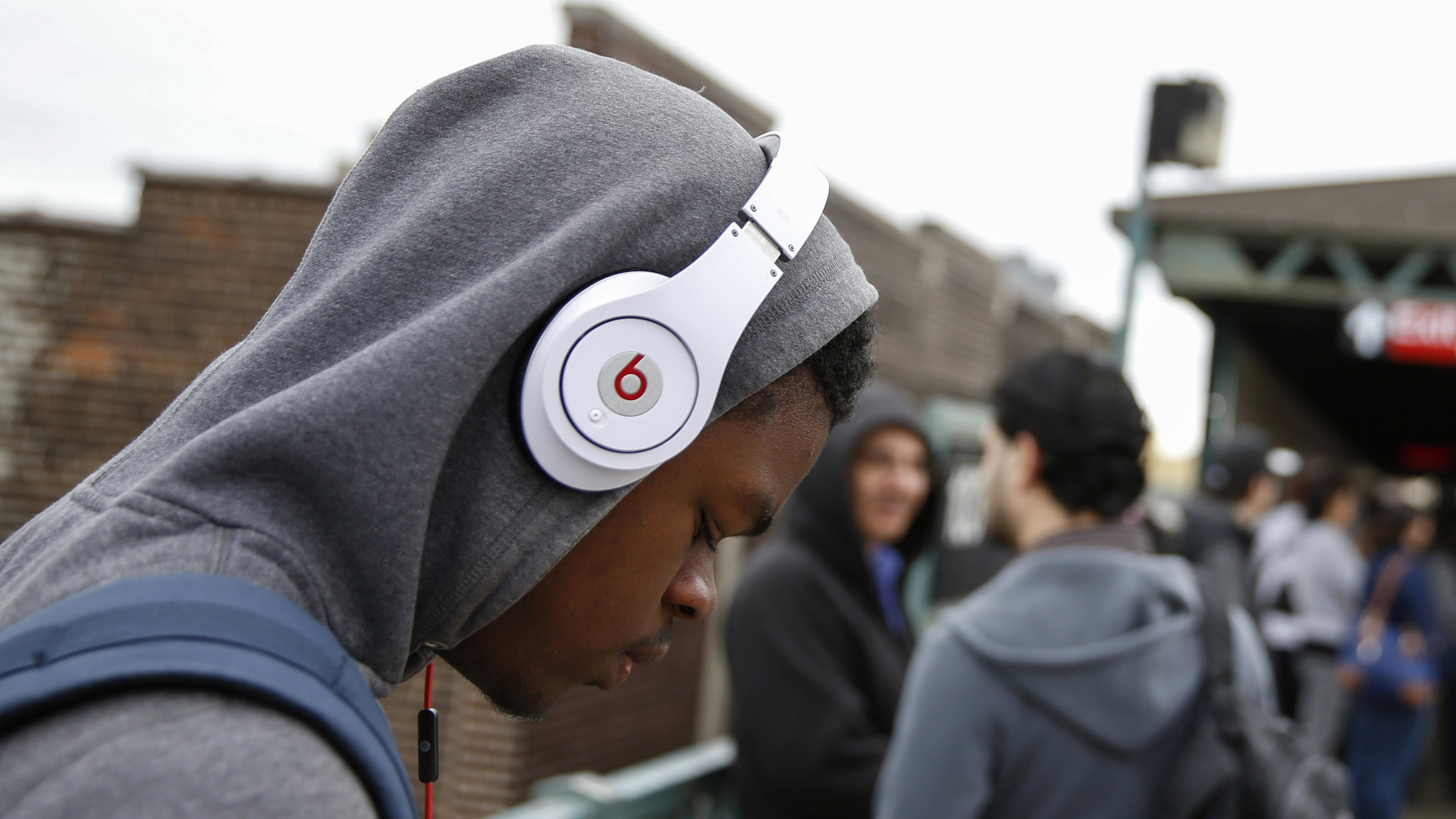 A commuter uses Beats brand headphones while waiting for the subway in New York May 29, 2014. Apple Inc will buy Beats for about $3 billion (1.79 billion pounds) and bring recording mogul Jimmy Iovine into its ranks, in a bid to make headway in the fast-growing music-subscription market. Through the acquisition, the iPhone maker also gains a line of high-end headphones popular with a young and urban demographic.  REUTERS/Shannon Stapleton   (UNITED STATES - Tags: BUSINESS) - RTR3REUL