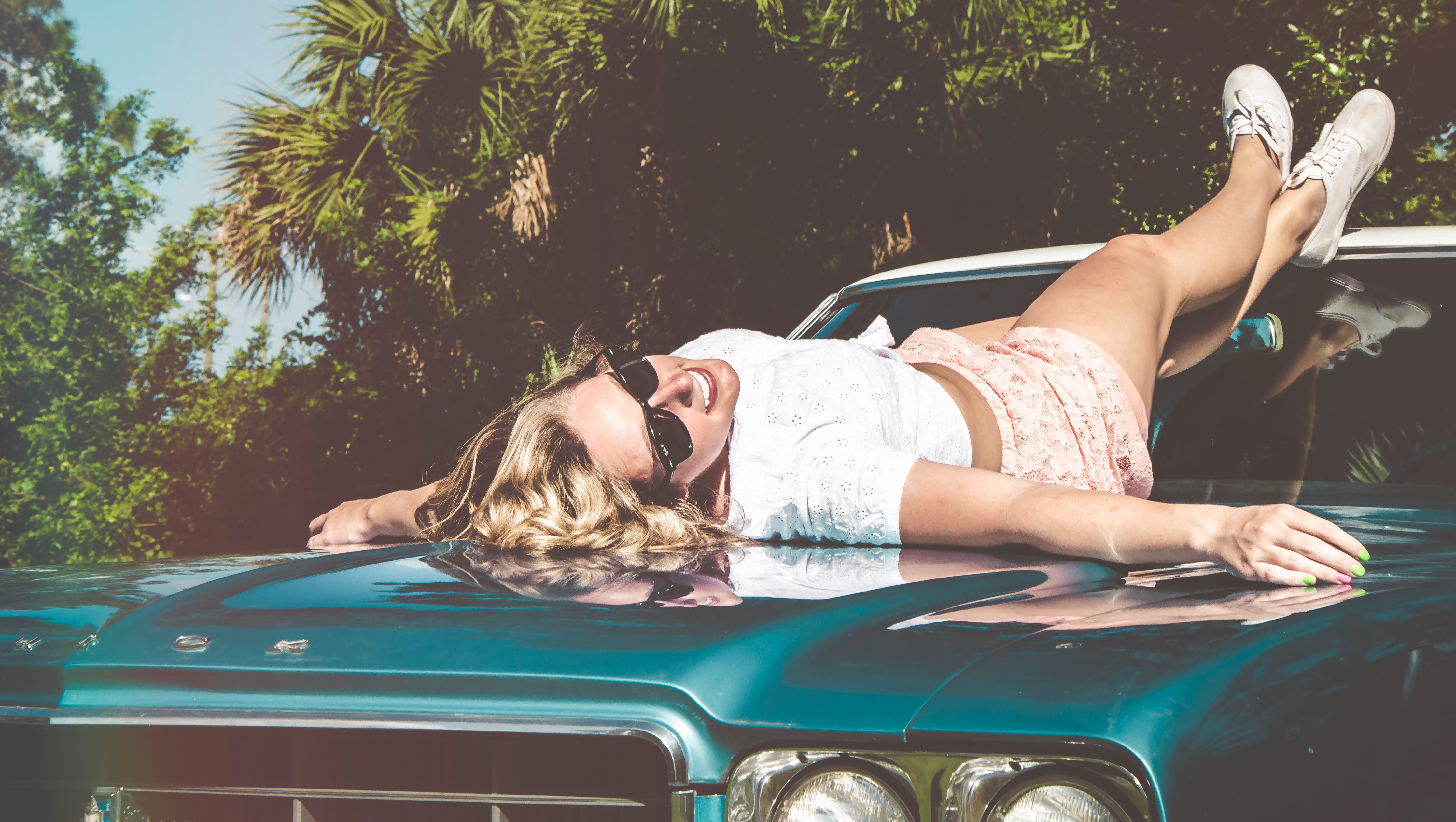 A woman lies on the hood of a car with her feet up on the car top