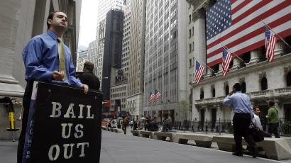 "Man holds ""bail us out"" sign outside Wall Street during financial crisis"