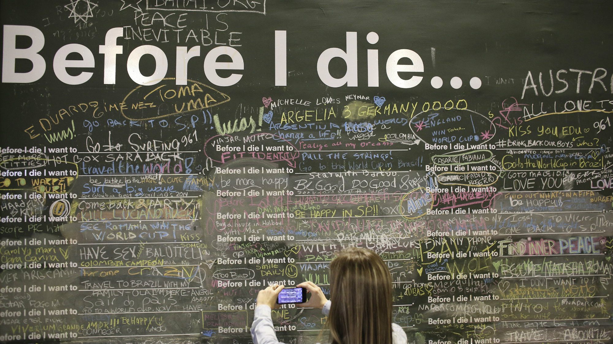 """A woman takes a picture of phrases written on a wall at a square in Sao Paulo July 3, 2014. The hoarding asks """"Before I die I want to_."""" leaving pedestrians to finish off the sentence."""