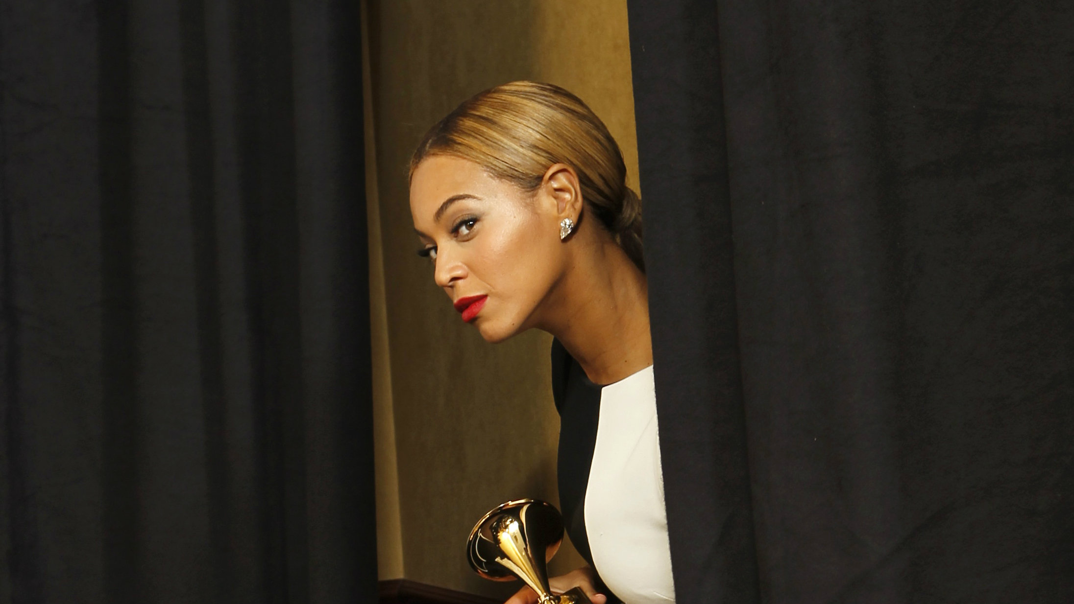 """Beyonce looks out at the photographers as she comes backstage to pose with her award for Best Traditional R&B Performance for """"Love On Top"""" at the 55th annual Grammy Awards in Los Angeles, California February 10, 2013. REUTERS/Mario Anzuoni (UNITED STATES - Tags: ENTERTAINMENT) (GRAMMYS-BACKSTAGE)"""