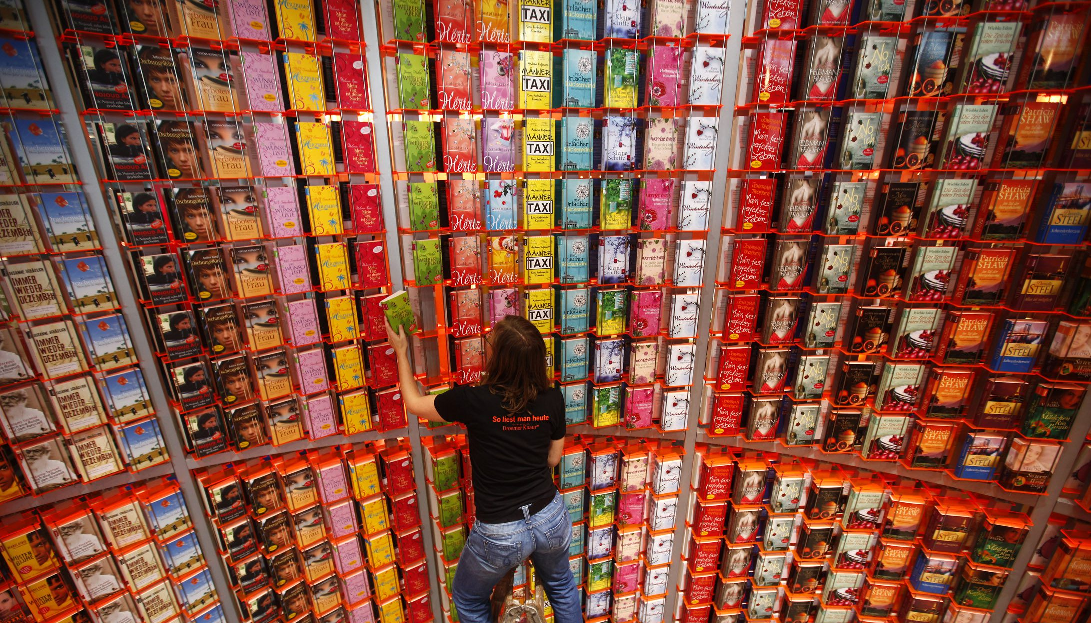Sylvia Fleischer of German publishing house Droemer Knaur makes final adjustments on a huge bookshelf prior to the opening of the book fair in Frankfurt, October 5, 2010.