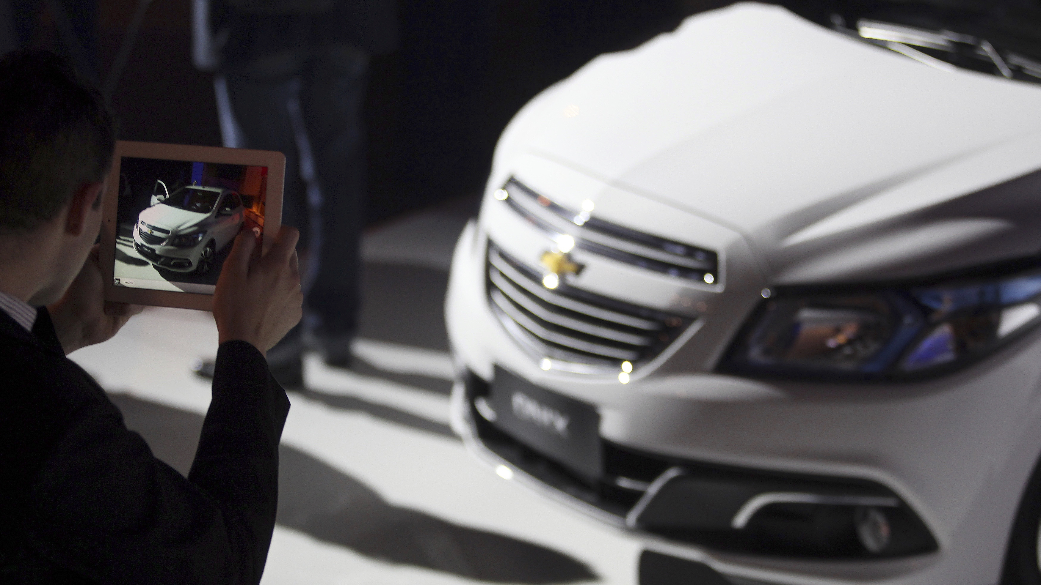 A person takes a photograph of the new Chevrolet Onix during the Chevrolet Onix World Premiere in Sao Paulo October 21, 2012.  REUTERS/Paulo Whitaker  (BRAZIL - Tags: BUSINESS TRANSPORT) - RTR39EW9