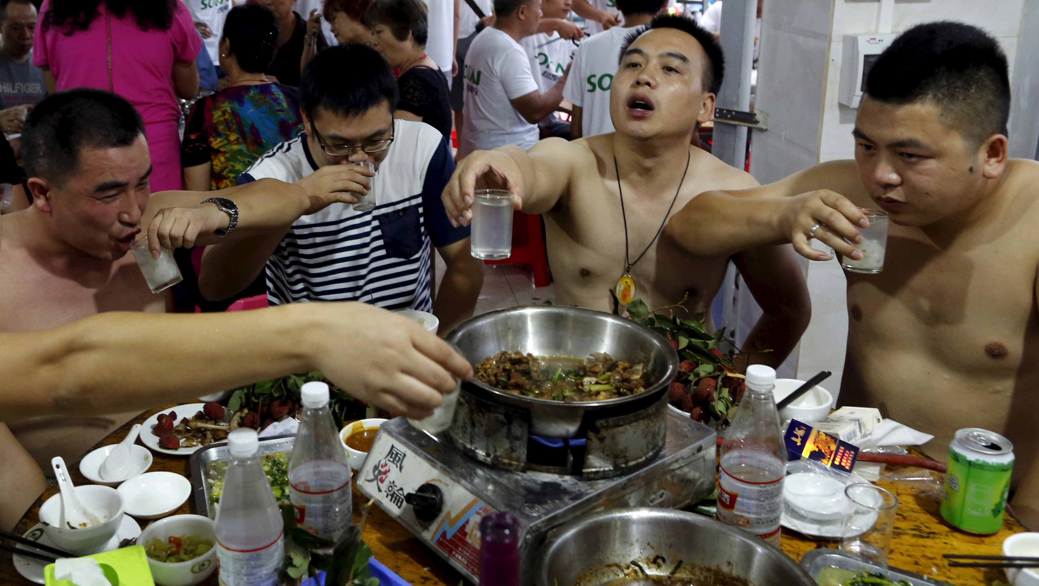 People toast over a dog meat dish at a dog meat restaurant on the day of local dog meat festival in Yulin, Guangxi Autonomous Region, June 22, 2015. For many residents of China's southern town of Yulin, the peak of summer is the perfect time to get together with family and friends - and consume copious amounts of dog meat. Thousands of dogs are expected to end up on the chopping block during the city's annual dog meat festival, which has become increasingly controversial in China. REUTERS/Kim Kyung-Hoon - RTX1HLHV