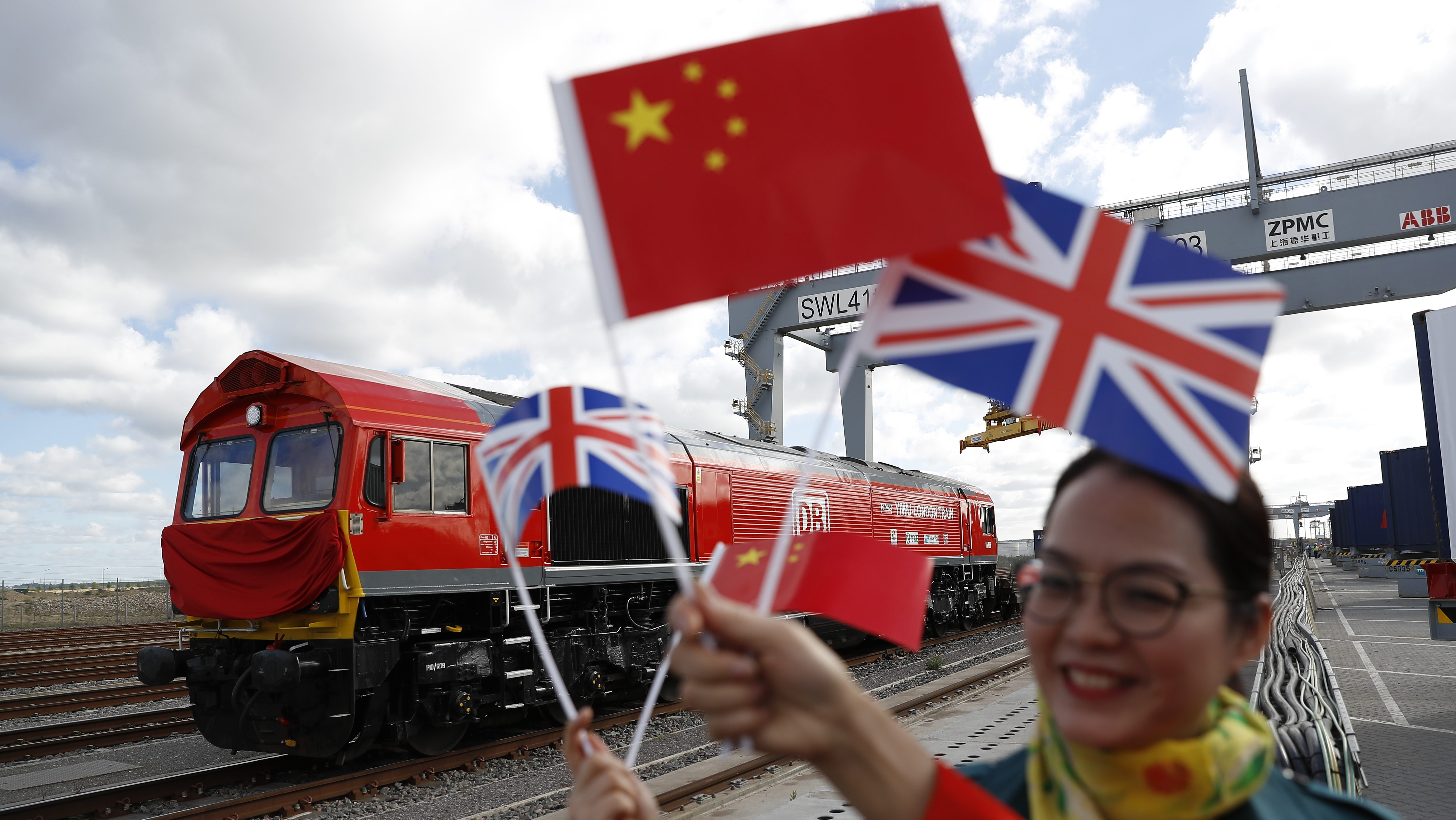Chinese women wave flags at the official ceremony to mark the departure of the first UK to China export train, laden with containers of British goods, from the DP World London Gateway, Stanford-le-Hope, Britain April 10, 2017. REUTERS/Peter Nicholls