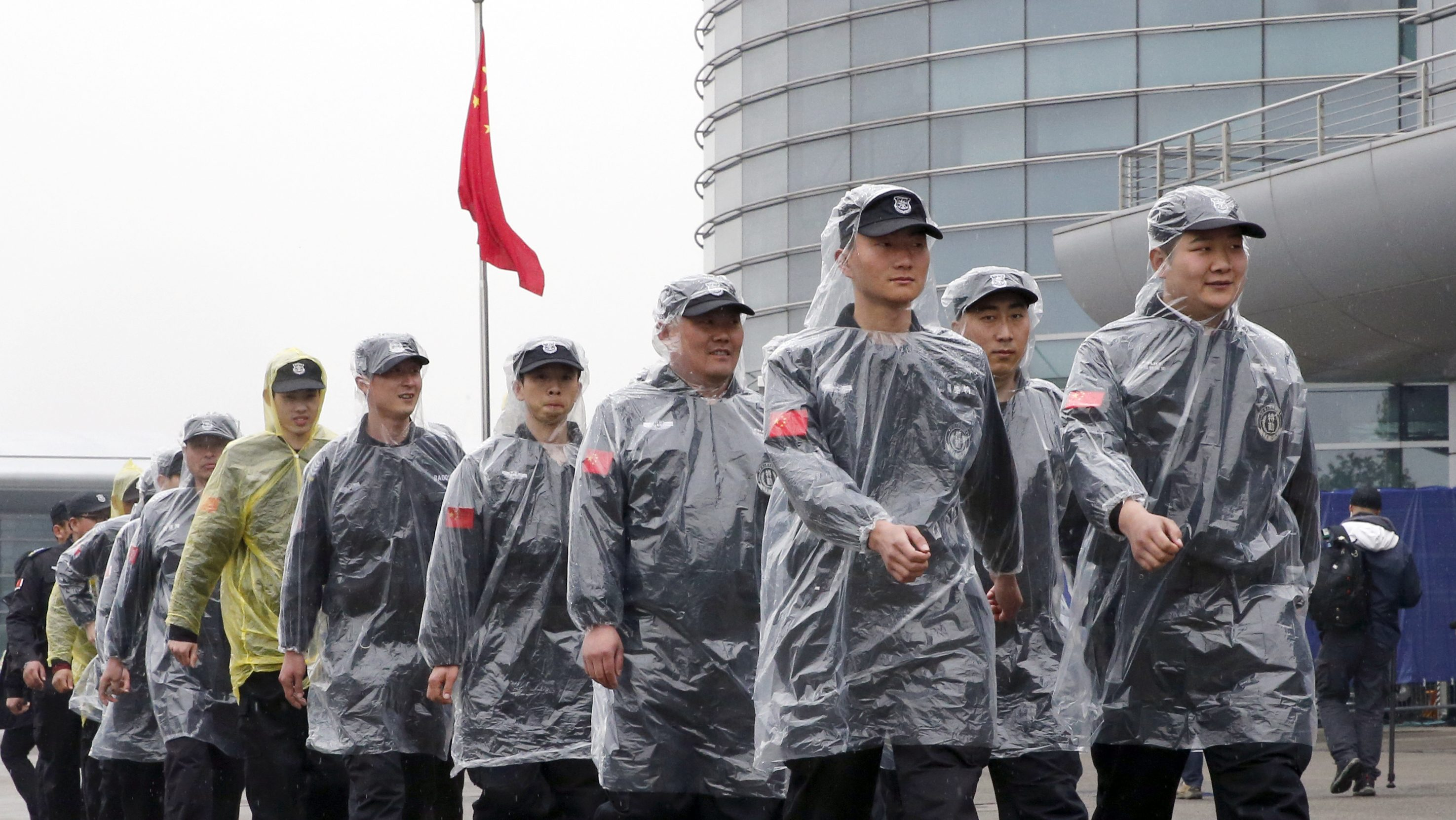 Security personnel wearing rain covers march at the paddock of the Shanghai International Circuit ahead of the Chinese Formula One Grand Prix at in Shanghai, China, Friday, April 7, 2017. The second practice session was canceled as the circuit's medical helicopter was unable to land at nearby hospitals or airports in case of an accident. (AP Photo/Toru Takahashi)