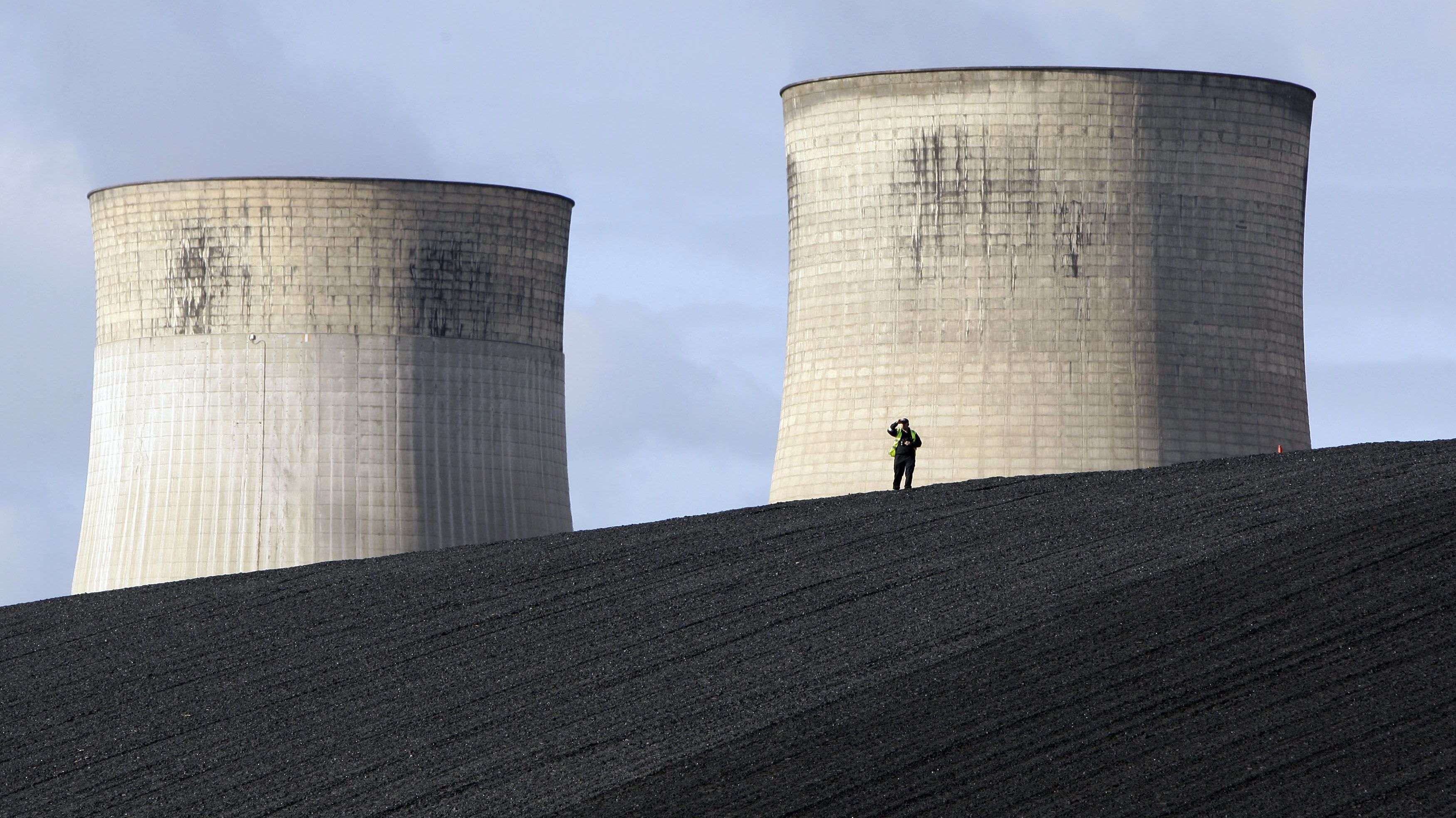 A security guard watches from a coal heap during a climate change protest at Ratcliffe Power Station at Ratcliffe-on-Soar, central England October 17, 2009.