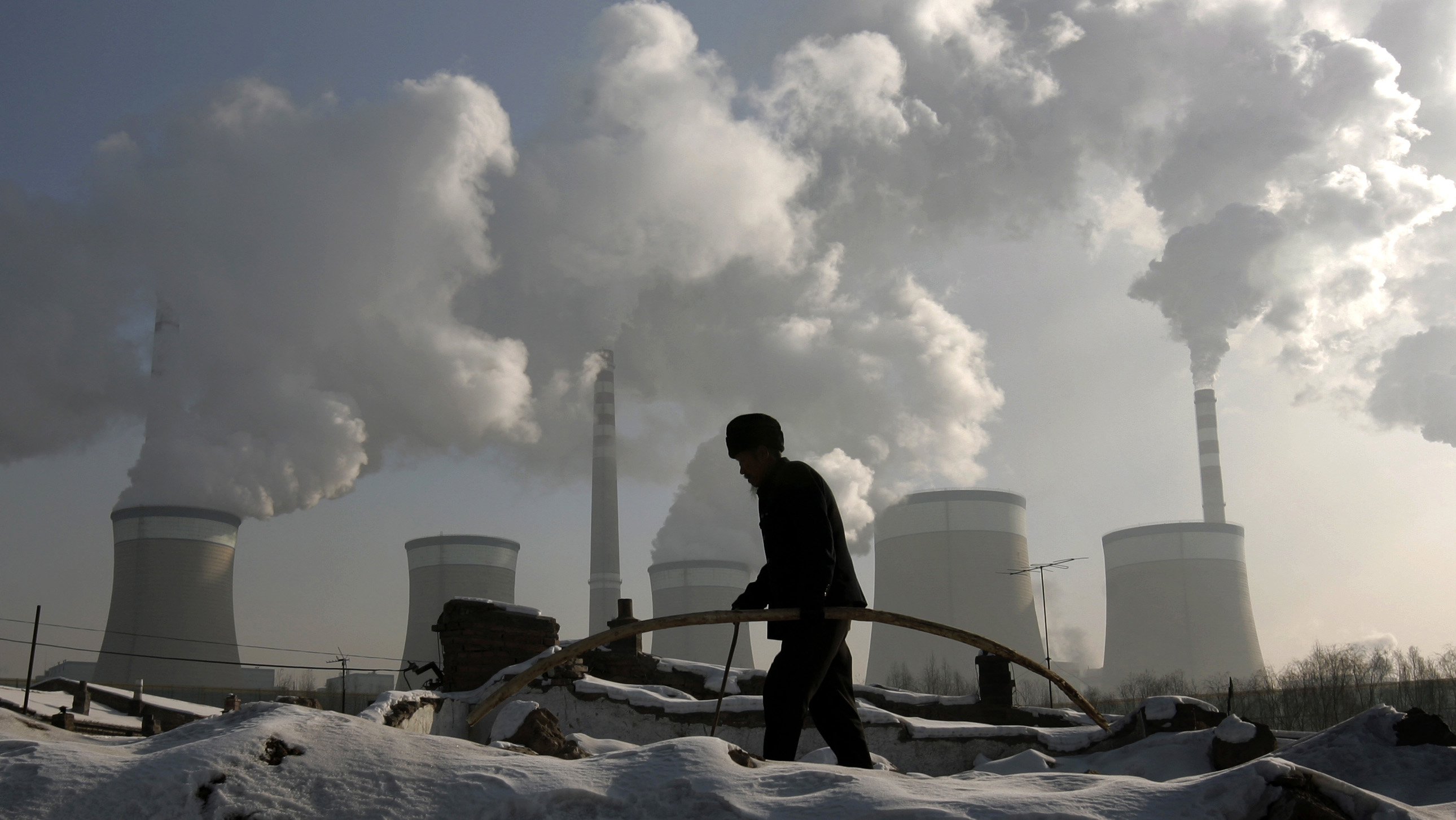 A villager walks in front of a coal-fired power plant on the outskirts of Datong, Shanxi province, November 20, 2009. China will raise power prices for non-residential users by around 5.4 percent from Friday, the first rise since July 2008, to compensate grid firms that lost out because of a government cap on prices. REUTERS/Jason Lee (CHINA ENERGY ENVIRONMENT BUSINESS IMAGES OF THE DAY) - RTXQXVL