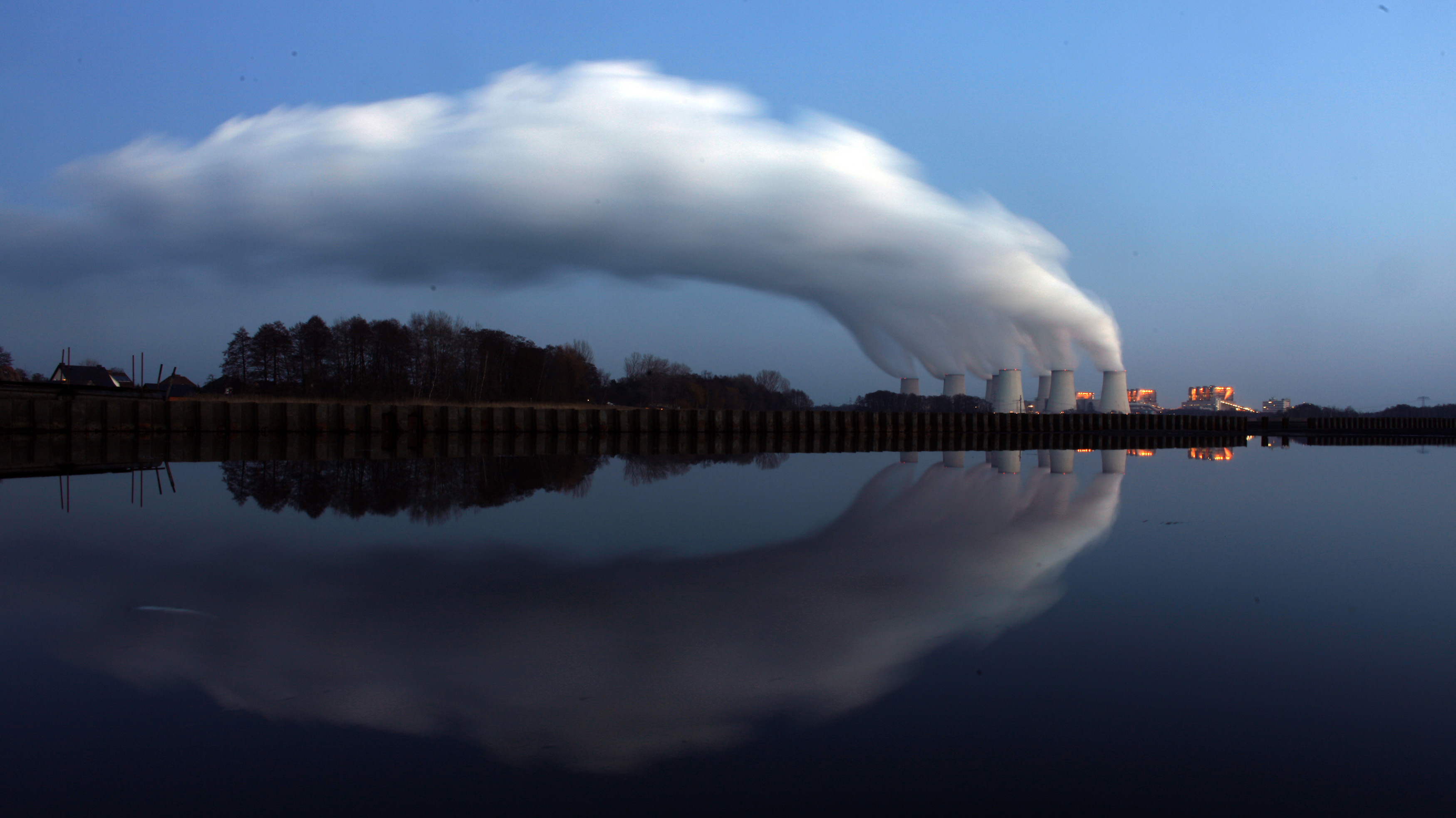 Steam billowing from the cooling towers of Vattenfall's Jaenschwalde brown coal power station is reflected in the water of a lake near Cottbus, eastern Germany December 2, 2009. Most world leaders plan to attend a climate summit in Copenhagen December 7-18, boosting chances that a new U.N. deal to fight climate change will be reached, host Denmark said on Tuesday. REUTERS/Pawel Kopczynski (GERMANY - Tags: ENVIRONMENT ENERGY) - RTXRDCW