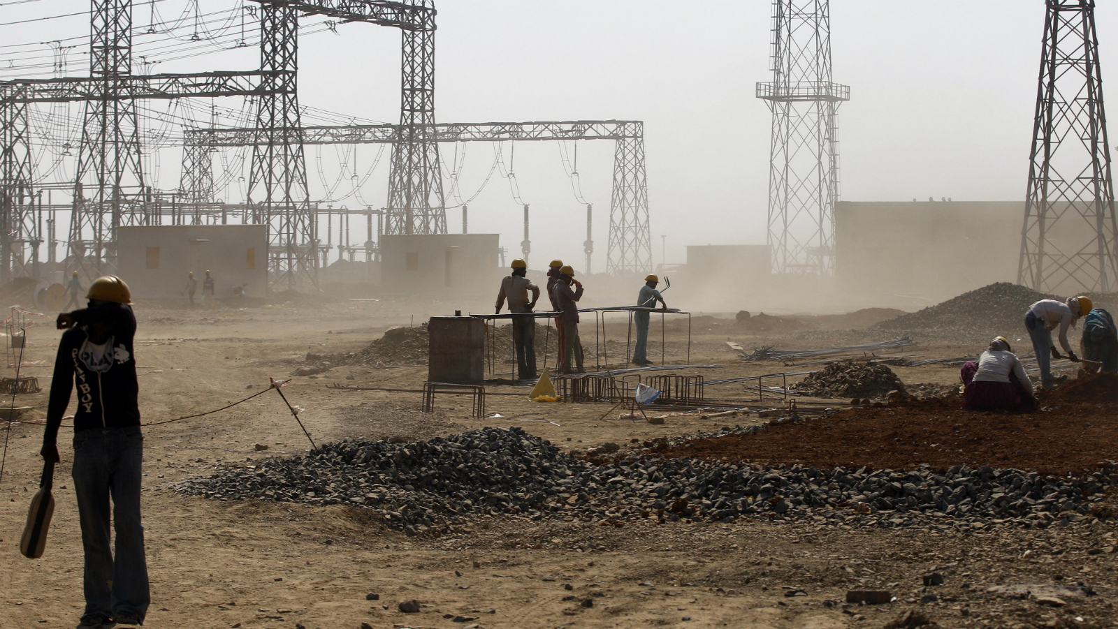 n this Feb. 24, 2015 file photo, a worker covers his face to avoid rising dust at a coal-fired power plant, partially financed by the Japan Bank for International Cooperation, under construction in Kudgi, India. Led by cutbacks in China and India, construction of new coal-fired power plants is falling worldwide, improving chances climate goals can be met despite earlier pessimism, three environmental groups said Wednesday, March 22, 2017. (File)