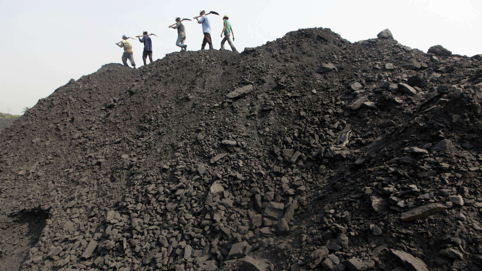 Workers walk on a heap of coal at a stockyard of an underground coal mine in the Mahanadi coal fields at Dera, near Talcher town in the eastern Indian state of Orissa March 28, 2012. India sits on the world's fifth-largest coal reserves, and produces the most after China and the United States. Picture taken March 28, 2012. To match INDIA-COAL/