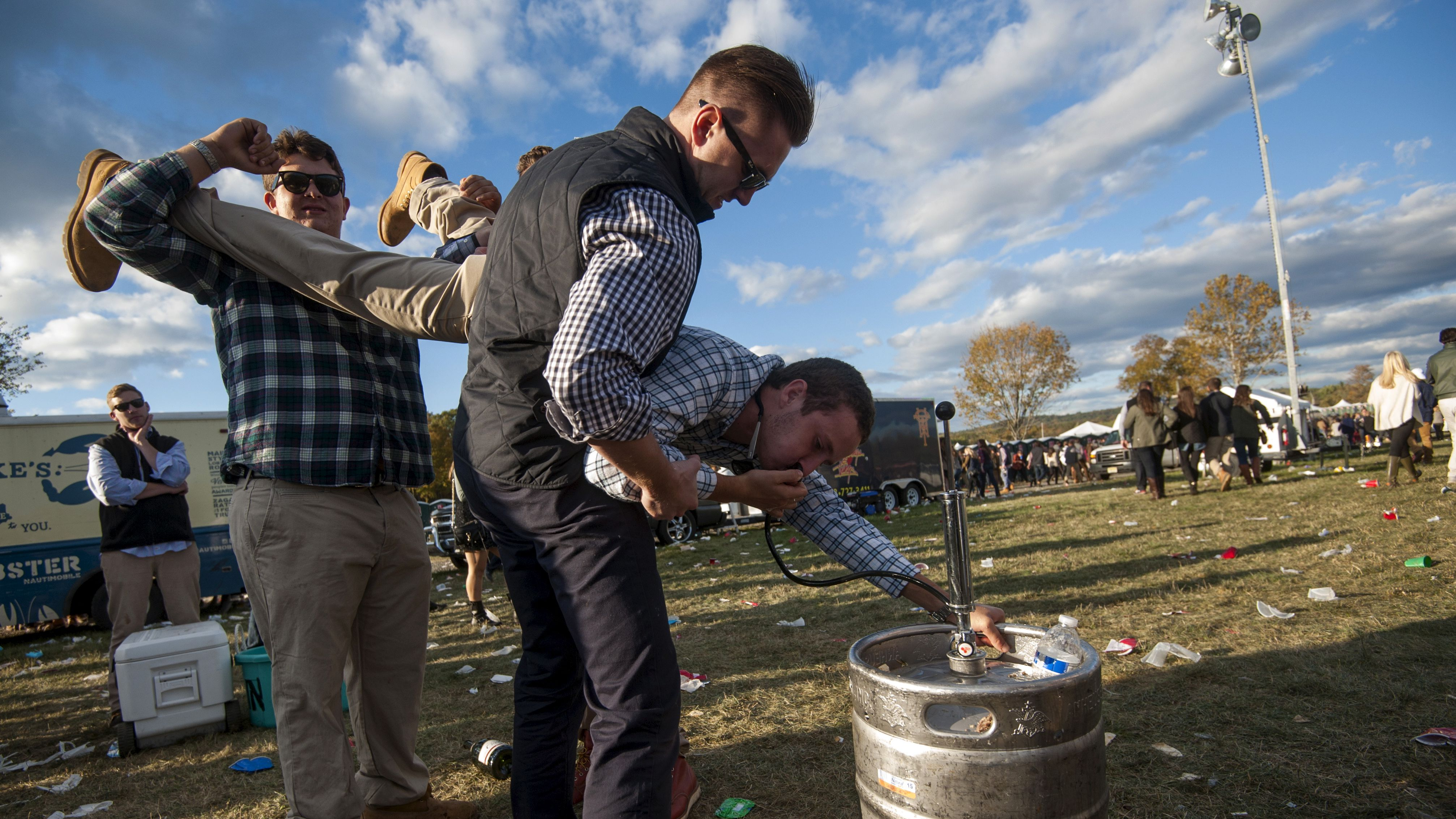 A man is held by friends as he drinks from a beer keg at the Far Hills Race Day at Moorland Farms in Far Hills, New Jersey, October 17, 2015. Young locals in New Jersey catch up with friends from school and college days at the Far Hills Race Day, which started as a fox-hunting event in the early 1900s. Many racegoers first went to the Hunt, as it's known locally, as children, but nowadays it's an alcohol-fuelled party for them. Makeshift bars are set up in cars, with the horses' efforts on the turf sometimes a backdrop to the main event. REUTERS/Stephanie Keith