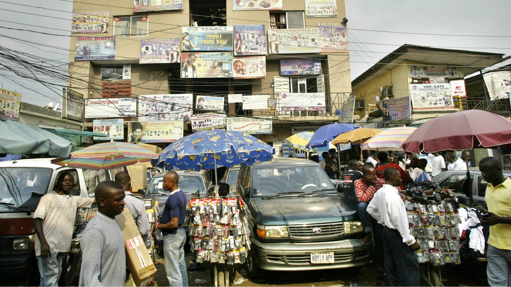 People buy telephones and computer software at the computer village in Lagos, Nigeria, Tuesday, March, 14 2006. Peddlers of pirated software now hold sway on the very streets where drug dealers and prostitutes plied their wares a decade ago in the Ikeja district of Nigeria's biggest city of Lagos. Where renowned musician Fela Anikulapo-Kuti appeared at the popular stage venue, every building is now packed with computer and cell phone companies and business is also done on the streets.