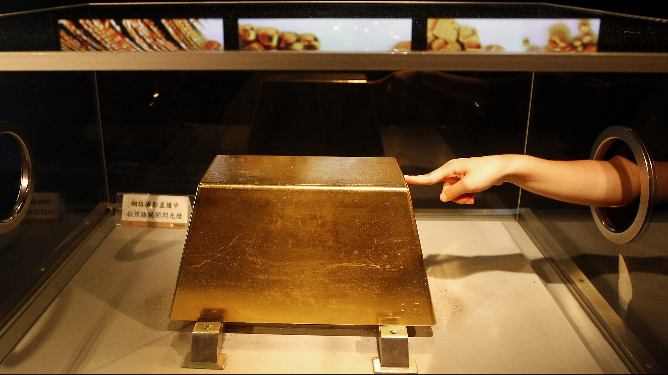 A visitor touches a 220 kg (485 lbs.) gold bar, worth around $12.8 million at today's price, on display at the Jinguashi Gold Ecological Park in Xinbei city September 16, 2011. The Jinguashi Gold Ecological Park said the gold bar is Taiwan's largest.