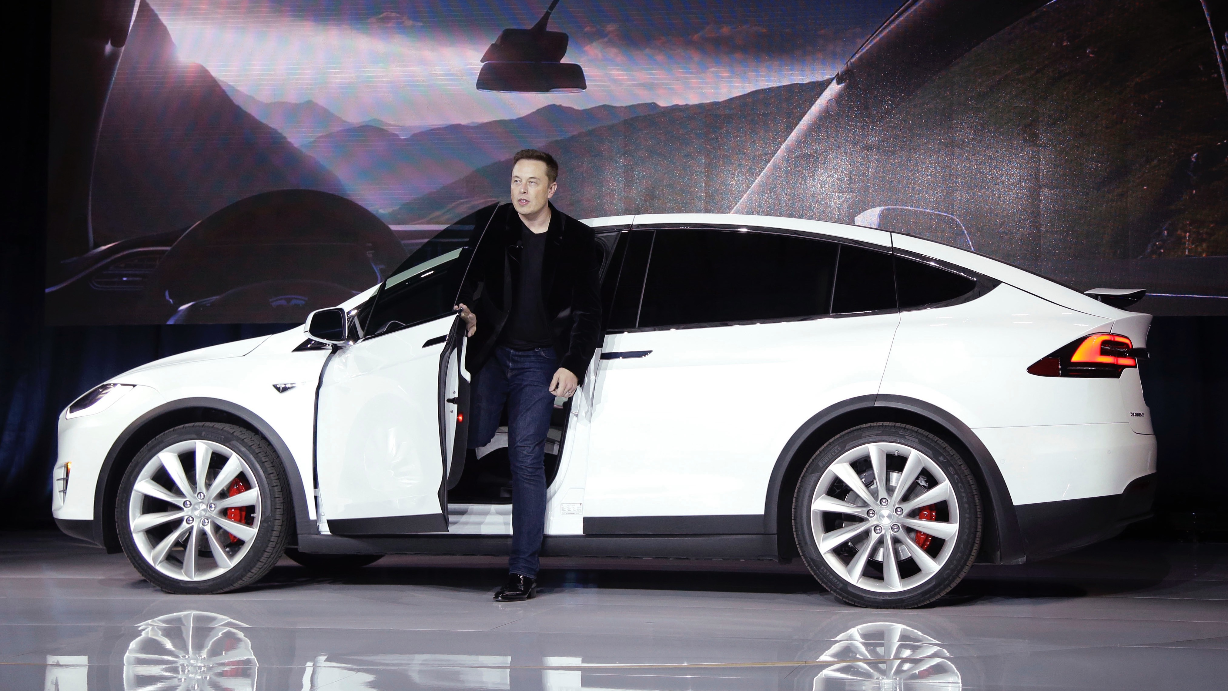 """FILE - In this Sept. 29, 2015 file photo, Elon Musk, CEO of Tesla Motors Inc., introduces the Model X car at the company's headquarters in Fremont, Calif. A Tesla in Autopilot mode can drive itself but it's not a """"self-driving"""" vehicle, at least as far as safety regulators are concerned. So, instead of coming under heavy government scrutiny before being sold to the public, Tesla can mass-produce cars that automatically adjust speed with the flow of traffic, keep their lane and slam the brakes in an emergency. (AP Photo/Marcio Jose Sanchez, File)"""