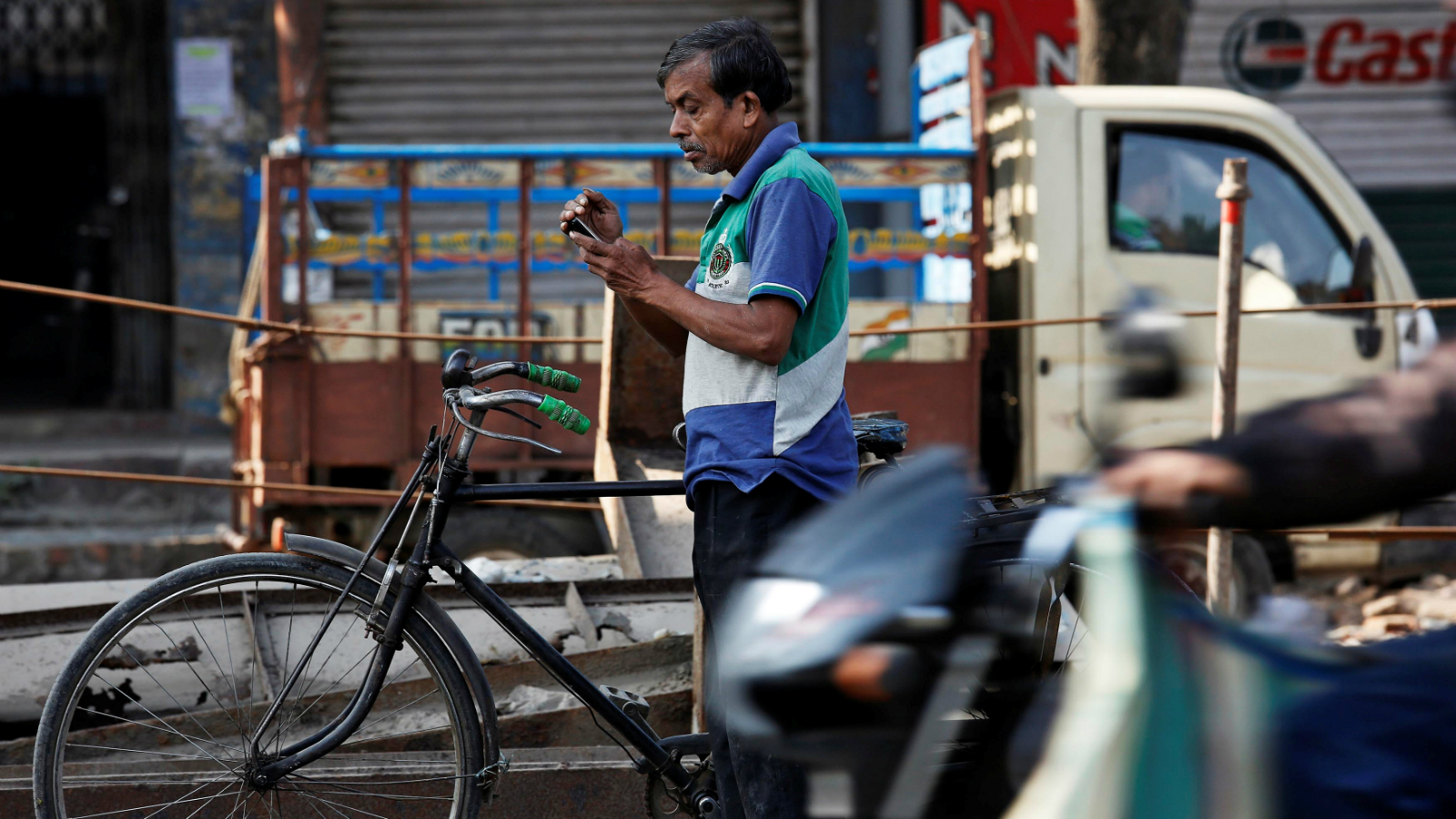 A man checks his mobile phone as he stands on a busy road in Kolkata, India January 6, 2017.