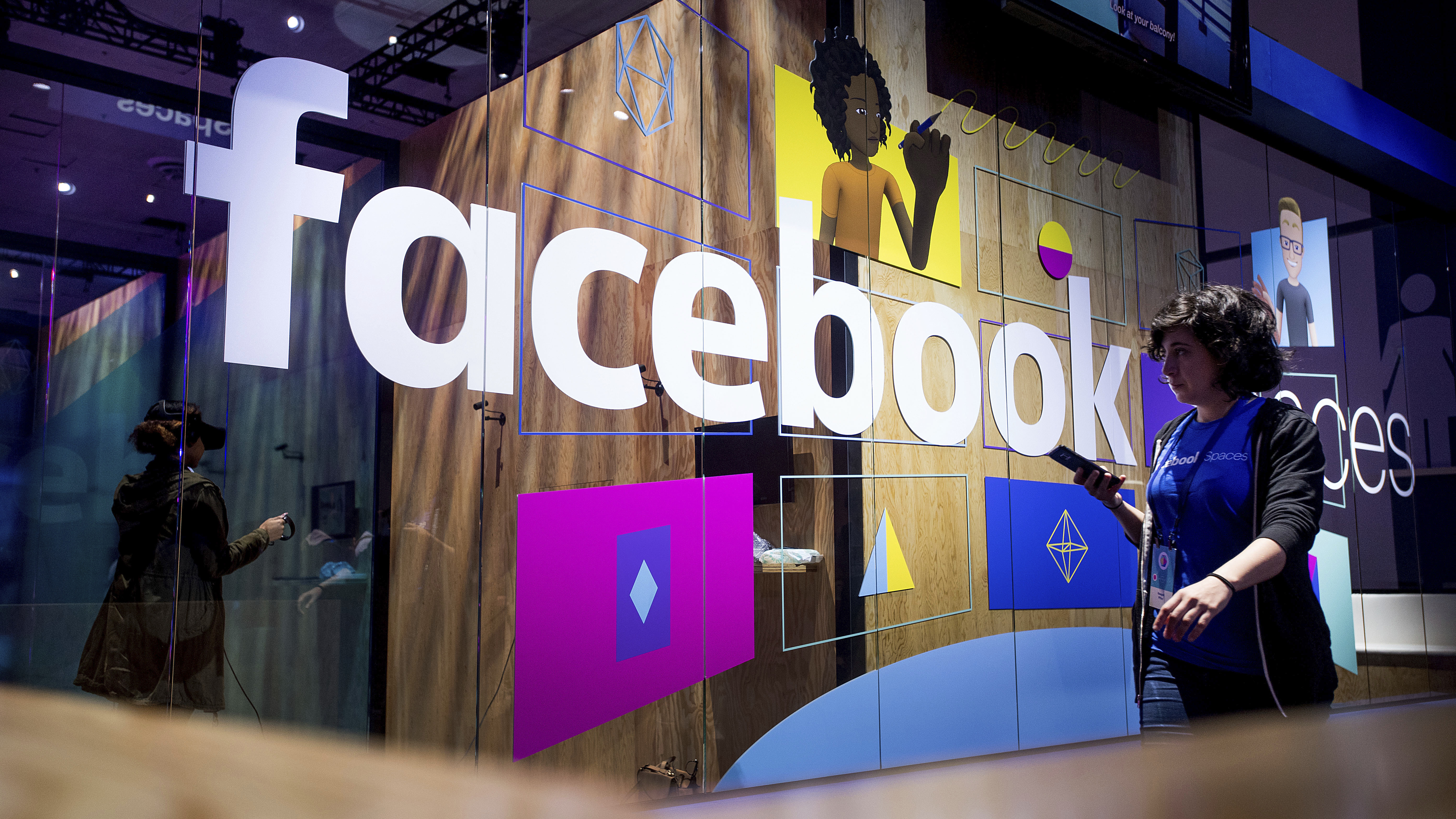 A conference worker passes a demo booth at Facebook's annual F8 developer conference, Tuesday, April 18, 2017, in San Jose, Calif. (AP Photo/Noah Berger)