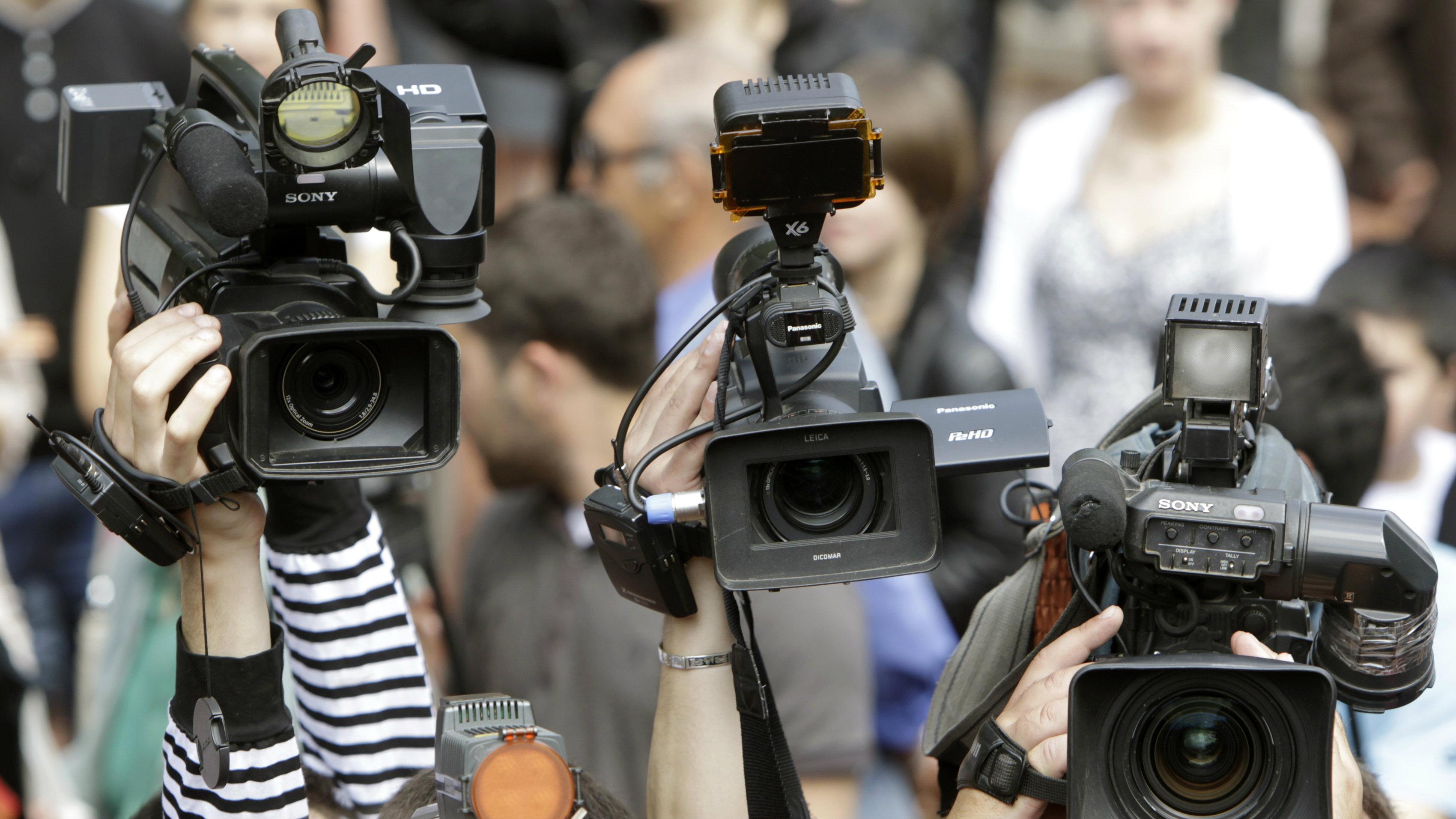 Cameramen lift their cameras to film in Tbilisi May 9, 2012. REUTERS/David Mdzinarishvili (GEORGIA - Tags: MEDIA)