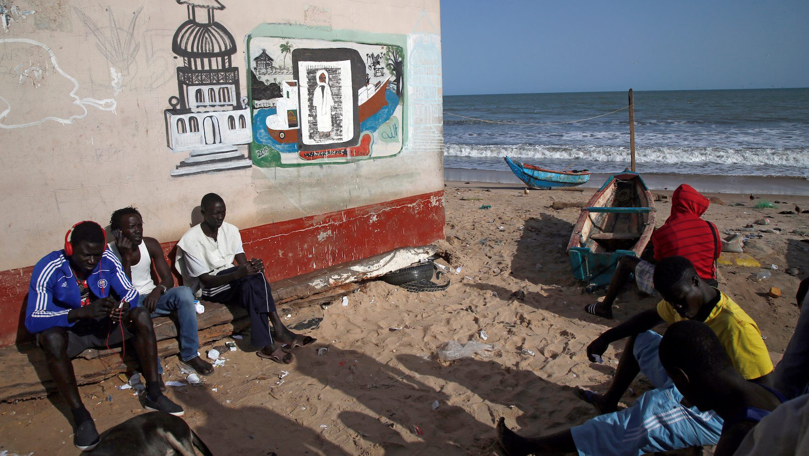 Fishermen are seen as they sit next to the seashore in Banjul, Gambia April 7, 2017.