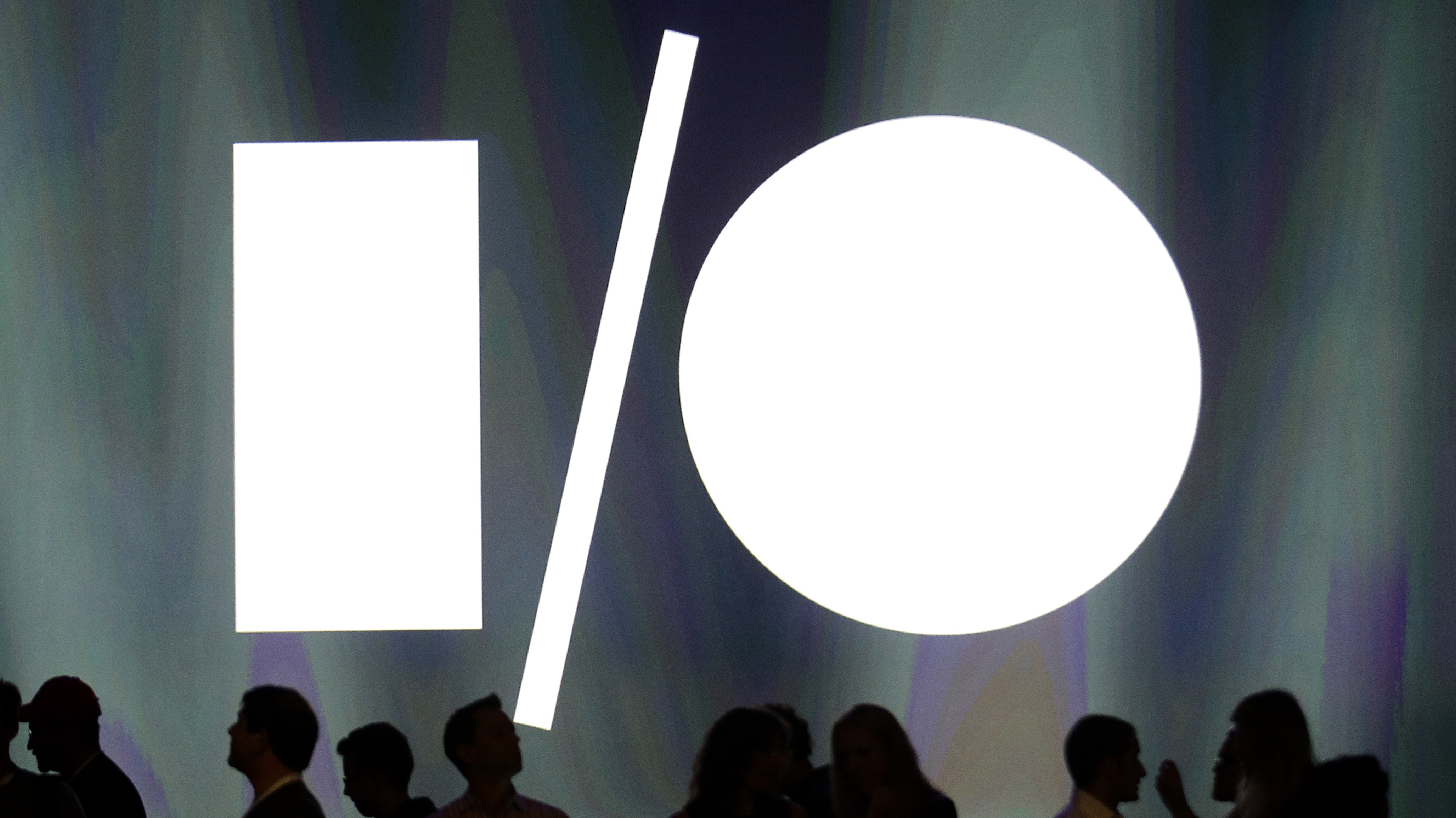 Attendees of the Google I/O 2014 keynote presentation stand in front of the screen at Moscone Center in San Francisco, Wednesday, June 25, 2014. Google is expected to reveal an Android update, smart home devices and other innovations at its two-day developer conference. (AP Photo/Jeff Chiu)