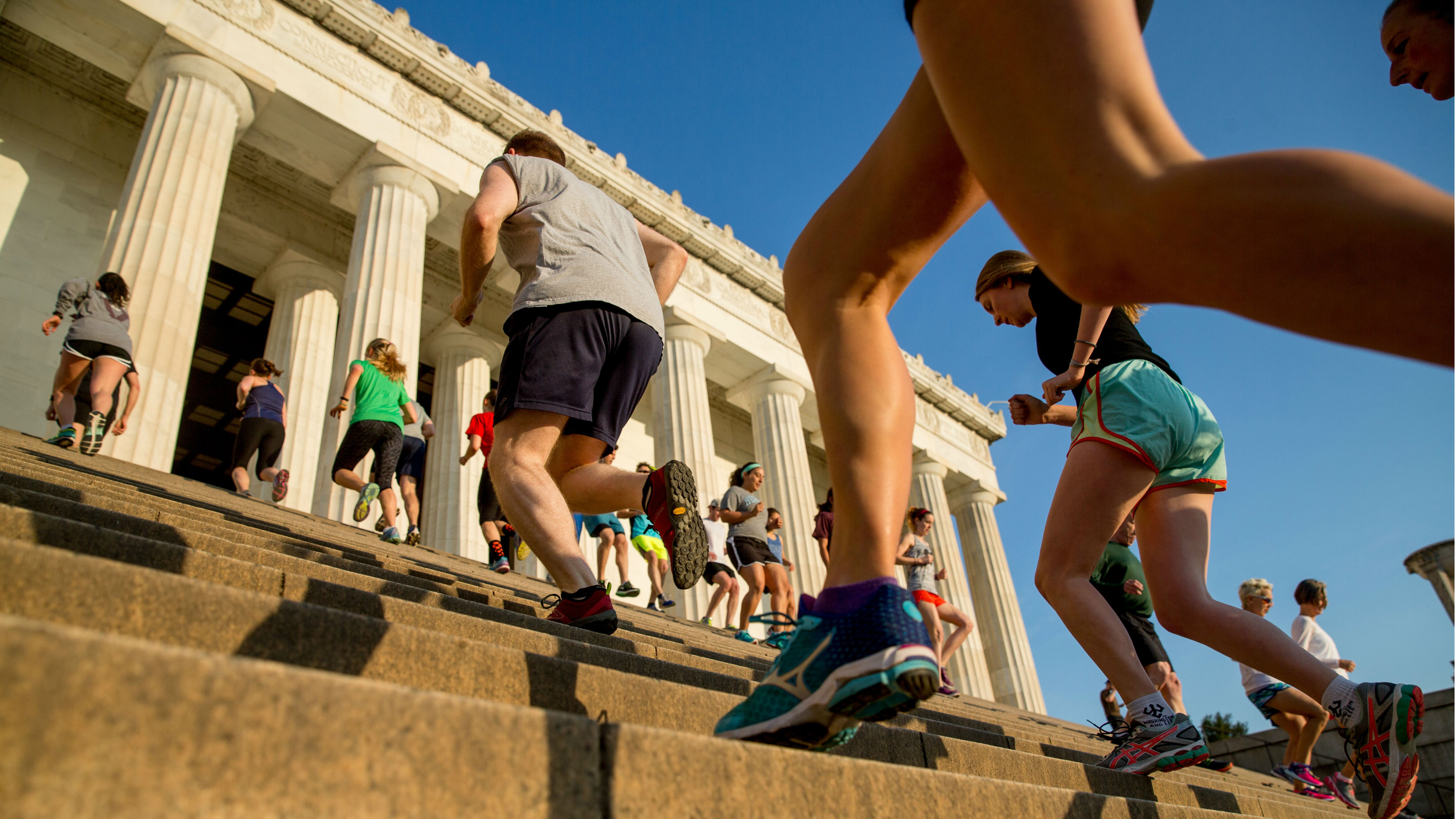 """In this May 25, 2016 photo, members of the running group """"November Project"""" run up and down the stairs of the Lincoln Memorial, in Washington. Fitness buffs around the country are bringing the 'take the stairs' advice to a whole new level as noteworthy landmarks have become unlikely, yet popular new workout sites."""